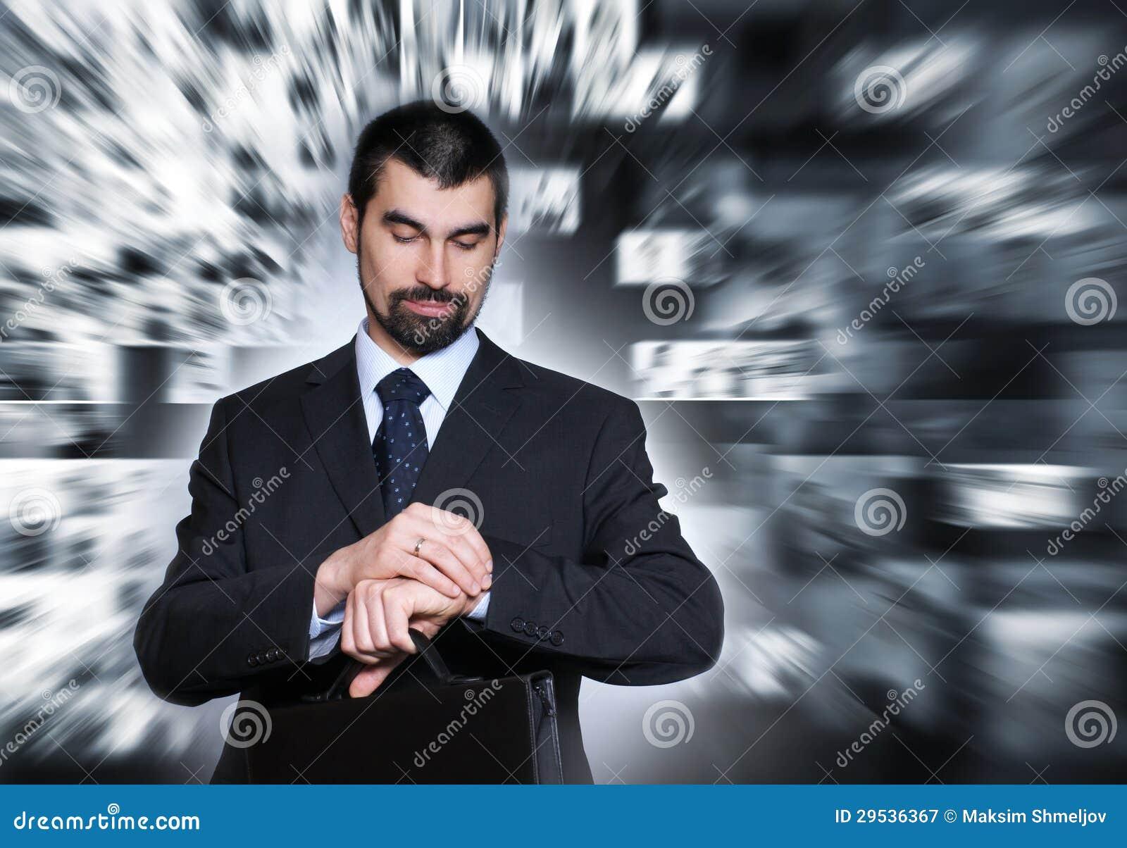 Um homem de negócios considerável na roupa formal que verifica o tempo