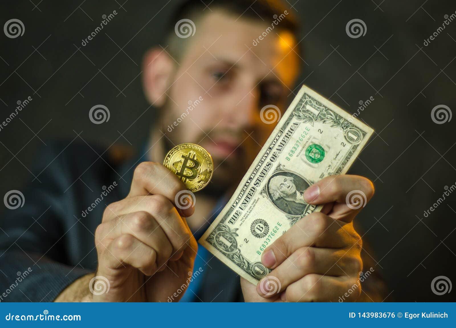 Um homem de negócios novo guarda uma moeda do bitcoite em sua mão
