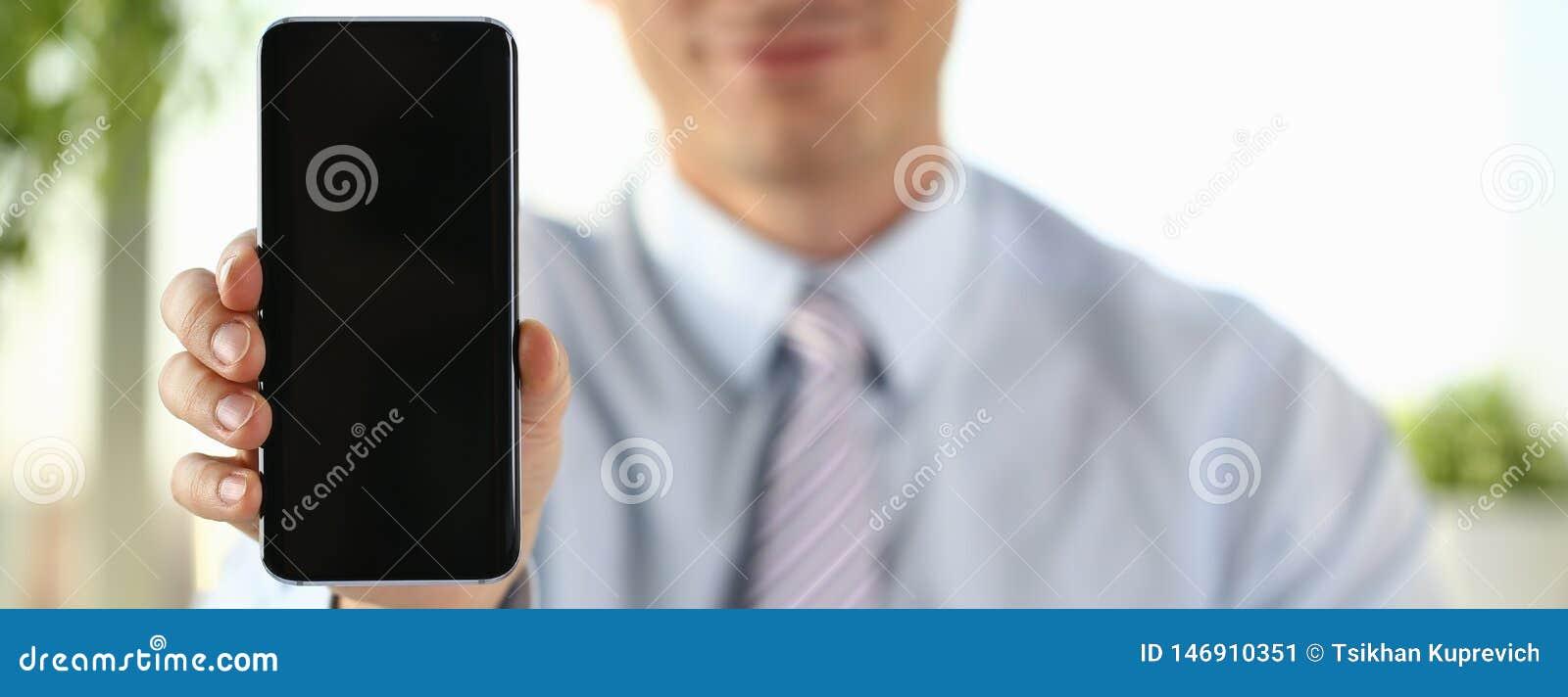 Um homem de neg?cios guarda um smartphone novo