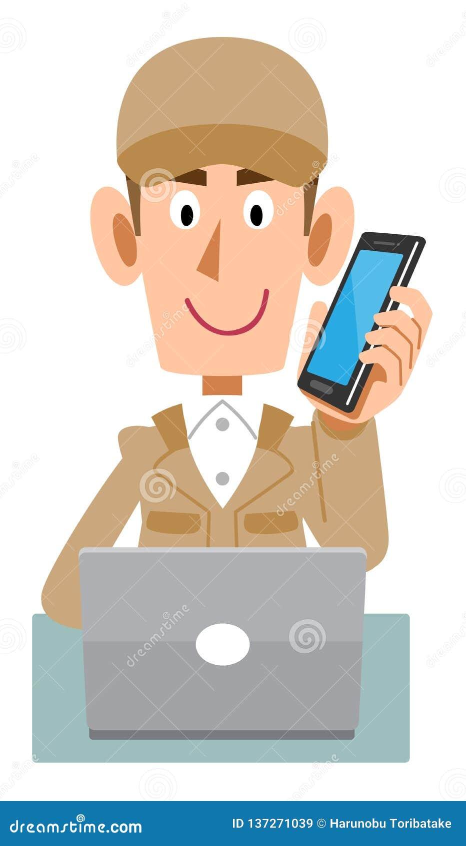 Um homem de trabalho que veste a roupa de trabalho bege para operar um computador ao falar no telefone celular