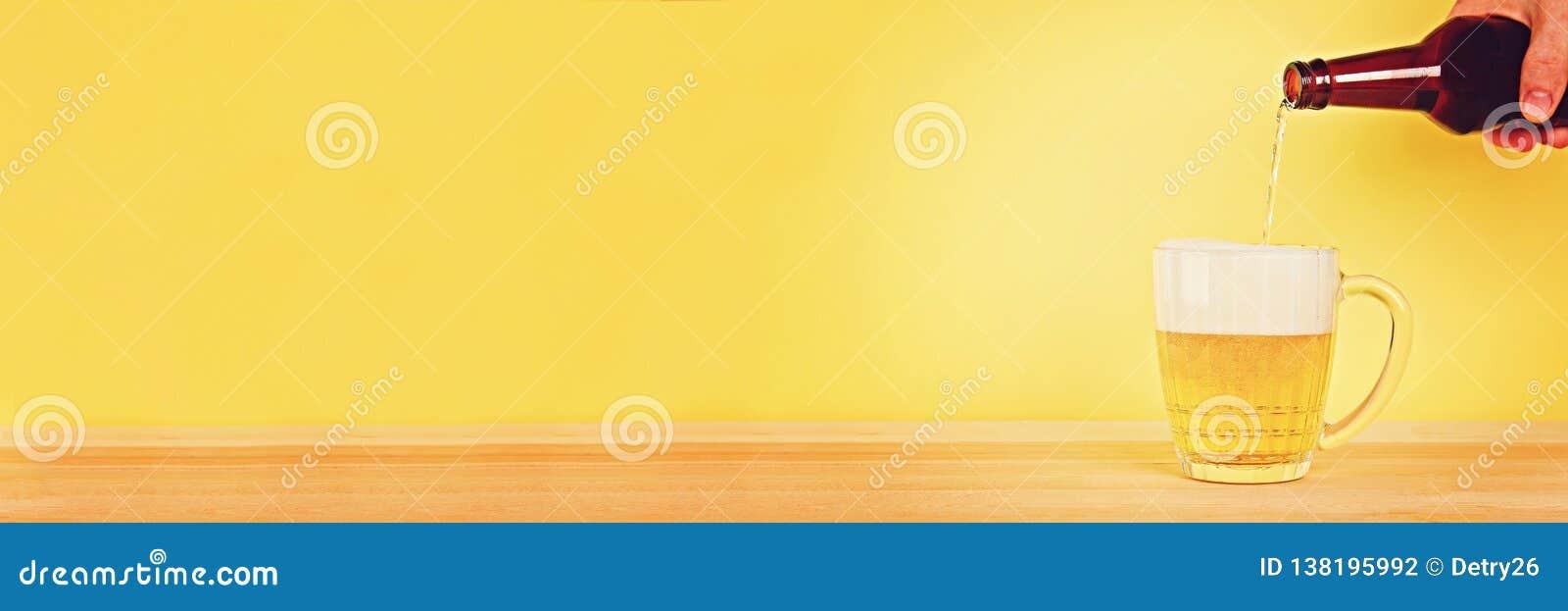 Um homem derrama a cerveja em uma caneca de uma garrafa em um fundo amarelo em uma tabela de madeira Copie o espaço
