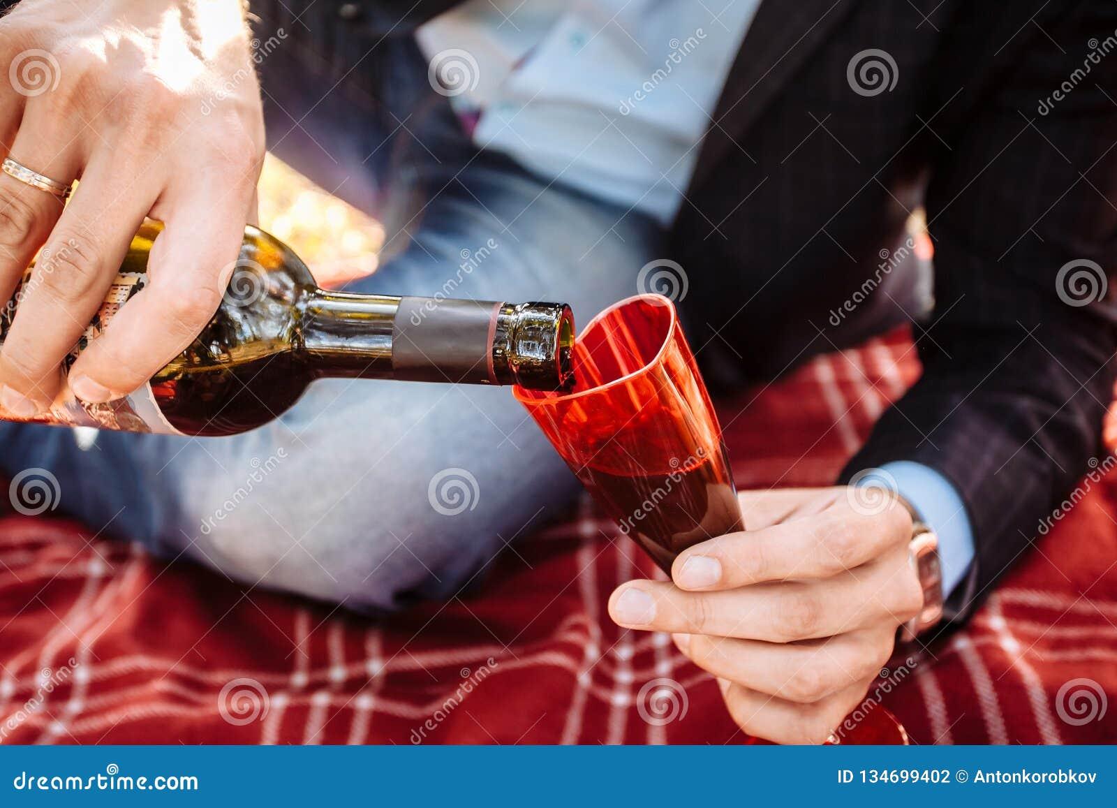 Um homem derrama o vinho em um vidro