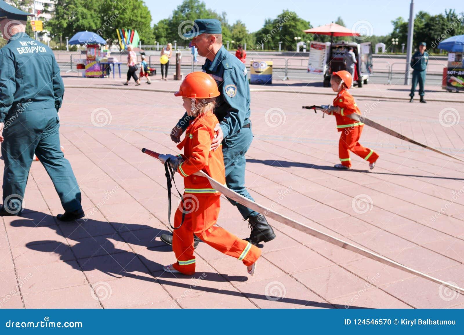 Um homem do ` s do bombeiro está ensinando uma menina em um terno à prova de fogo ornery correr ao redor com Bielorrússia, Minsk,