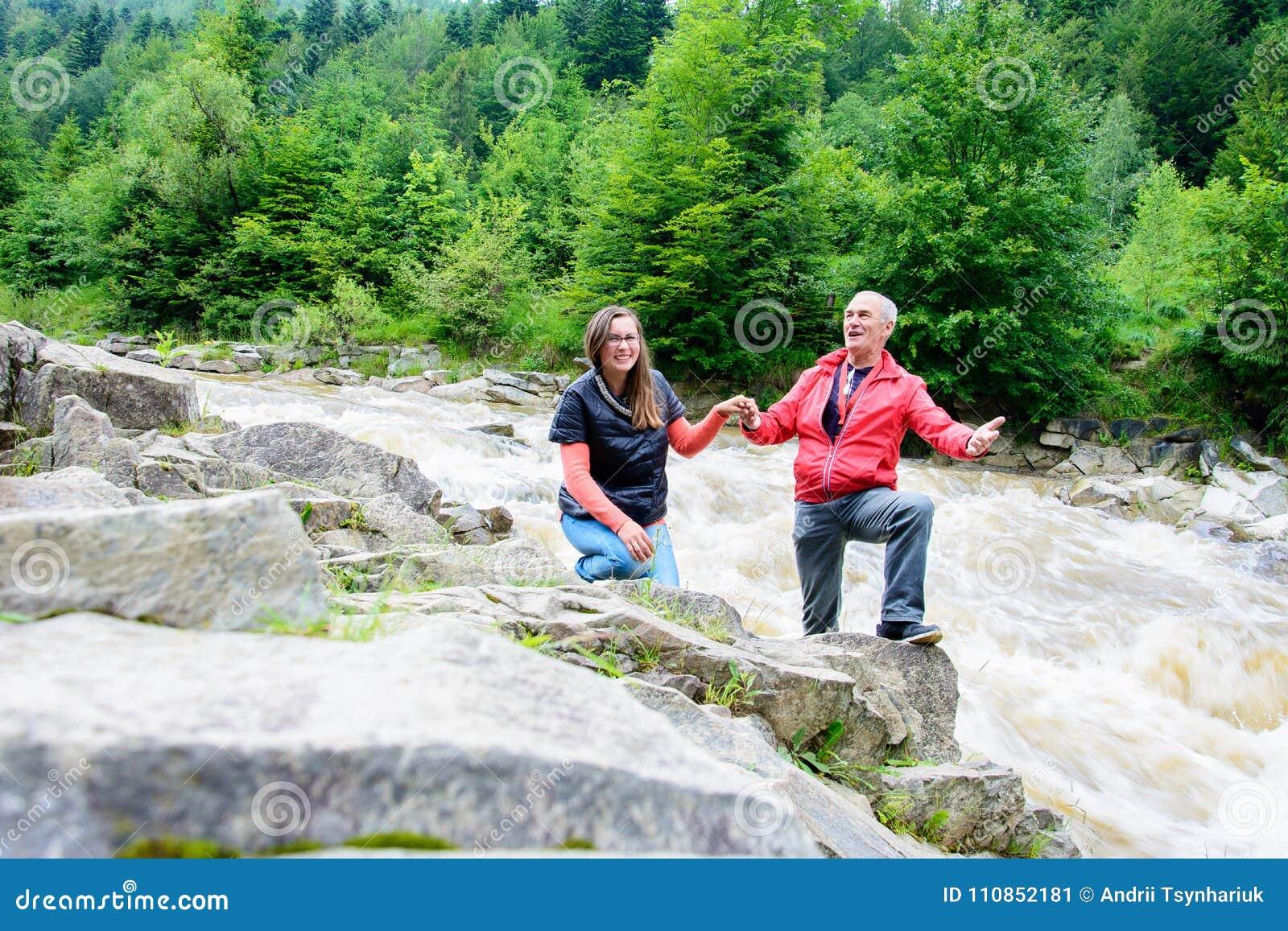 Um homem e uma mulher cantam nos Carpathians no fundo do rio