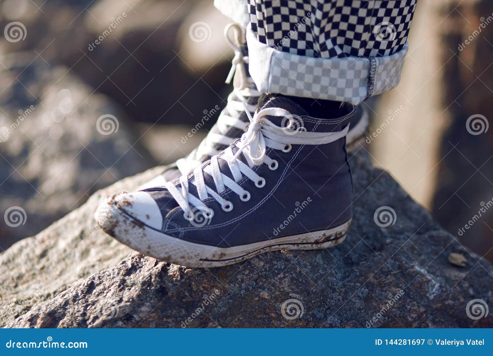 Um homem em suportes sujos azuis das sapatilhas em uma rocha