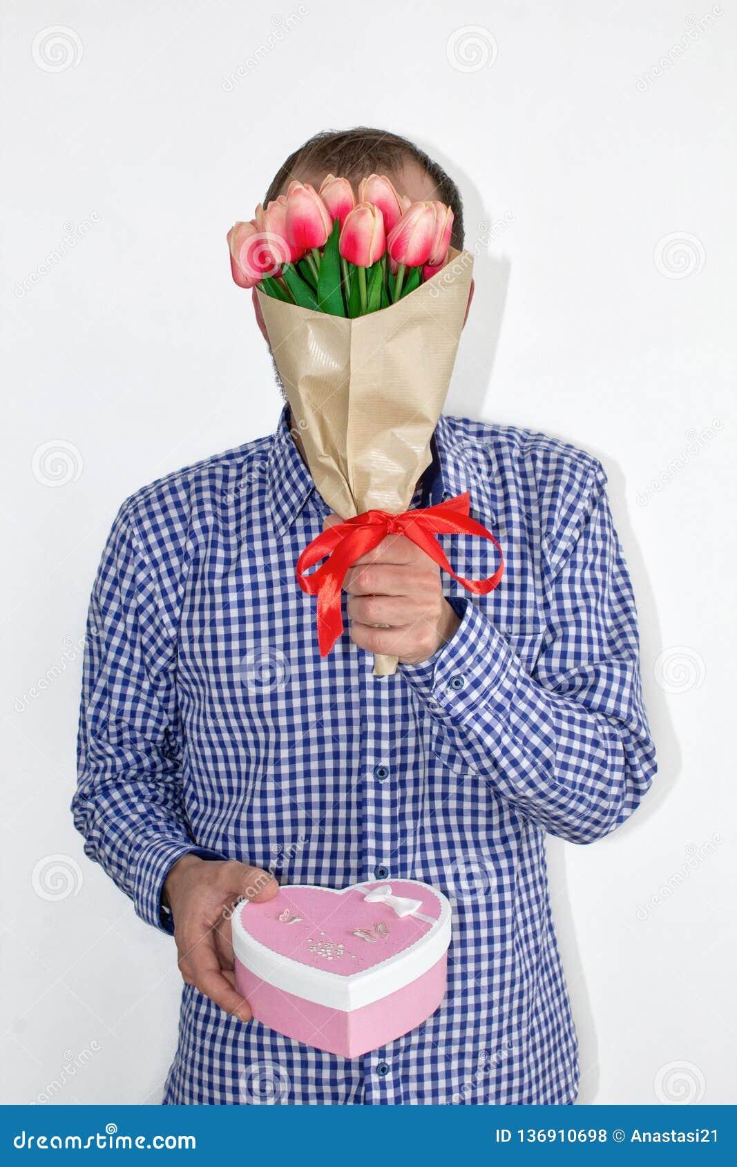 Um homem em uma camisa guarda flores das tulipas na frente de sua cara e guarda para fora uma caixa coração-dada forma em um fund