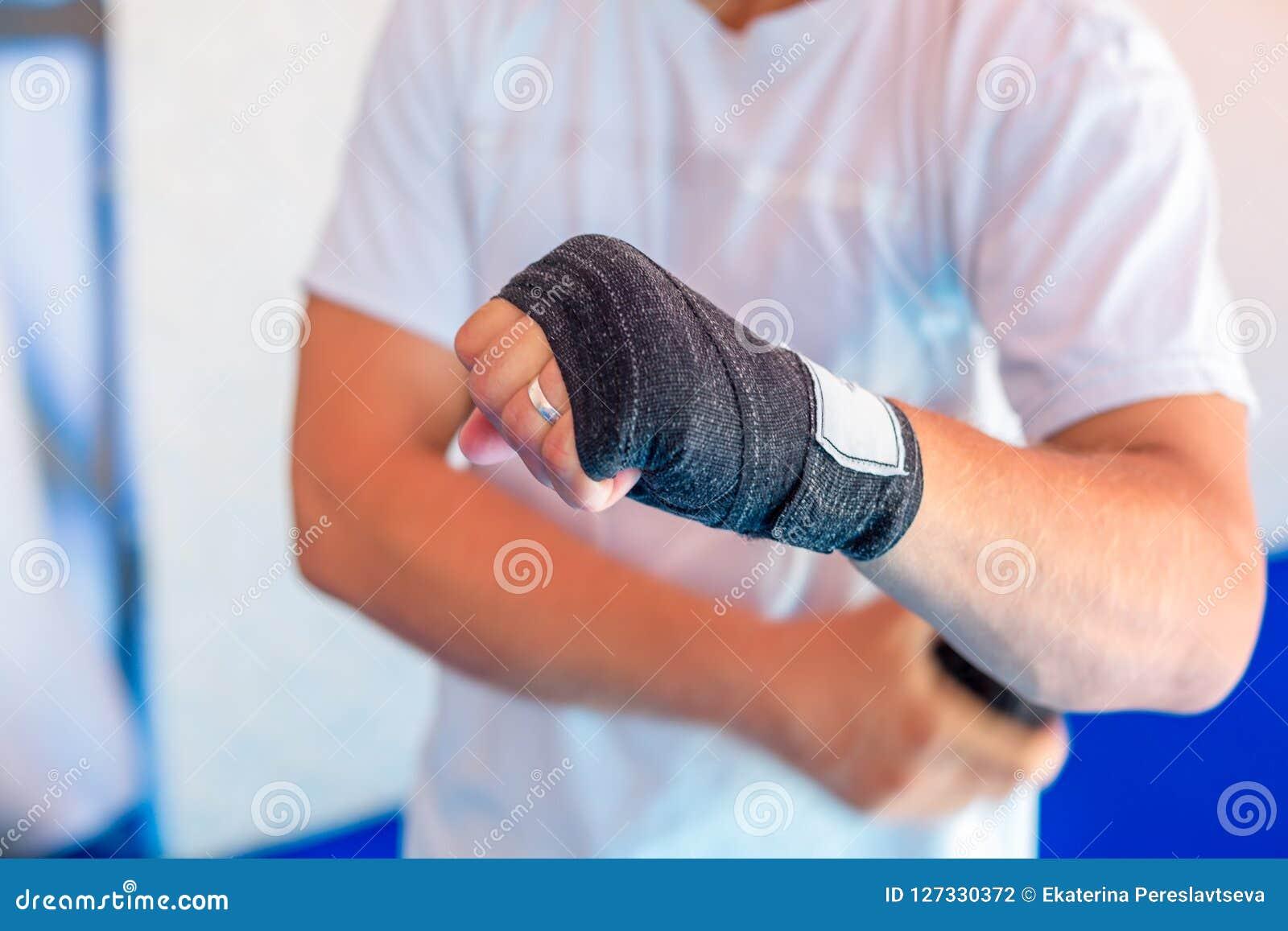 Um homem envolve as ataduras dos esportes em suas mãos
