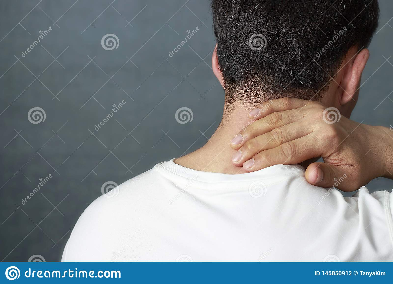 Um homem está fazendo massagens um pescoço dorido, close-up, vista traseira