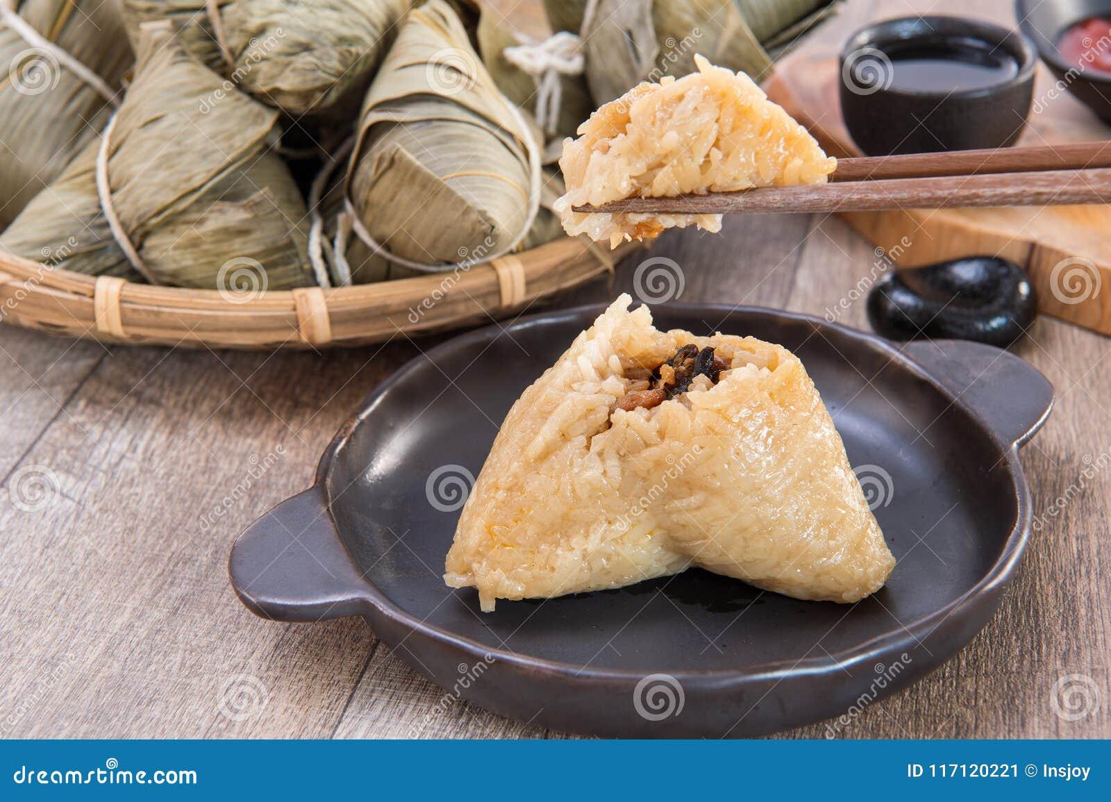 Um homem está indo comer a bolinha de massa do zongzi ou do arroz em Dragon Boat Festival