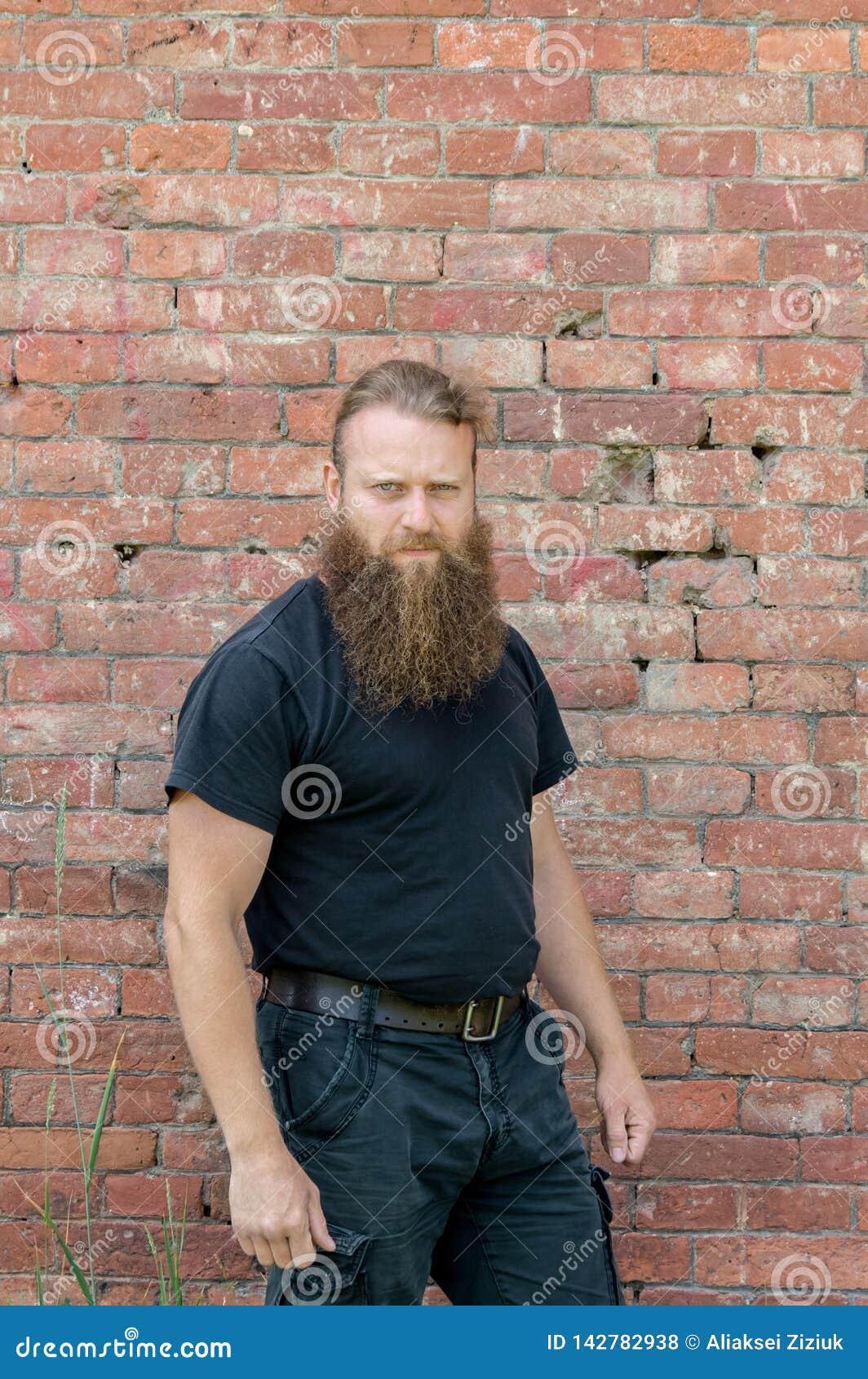 Um homem, um europeu com uma barba, está meio uma volta no fundo de uma parede vermelha do kerf