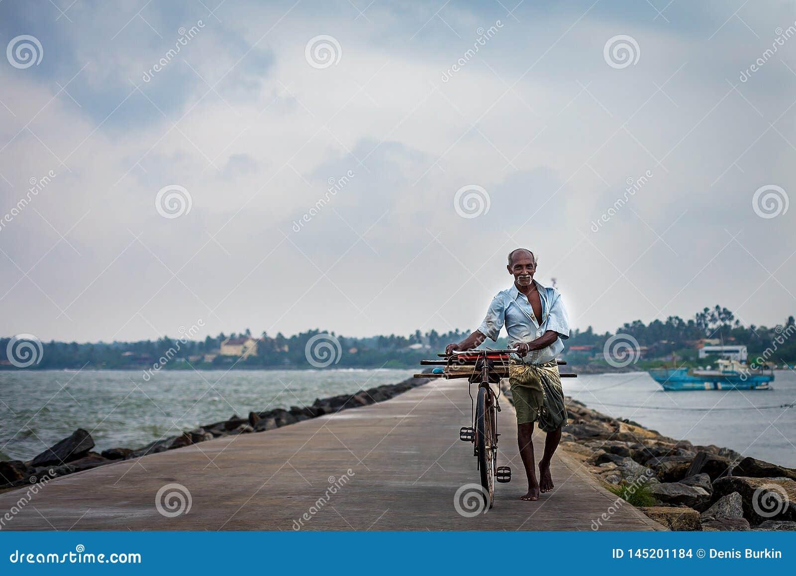 Um homem idoso estranho leva uma bicicleta ao longo da costa do oceano