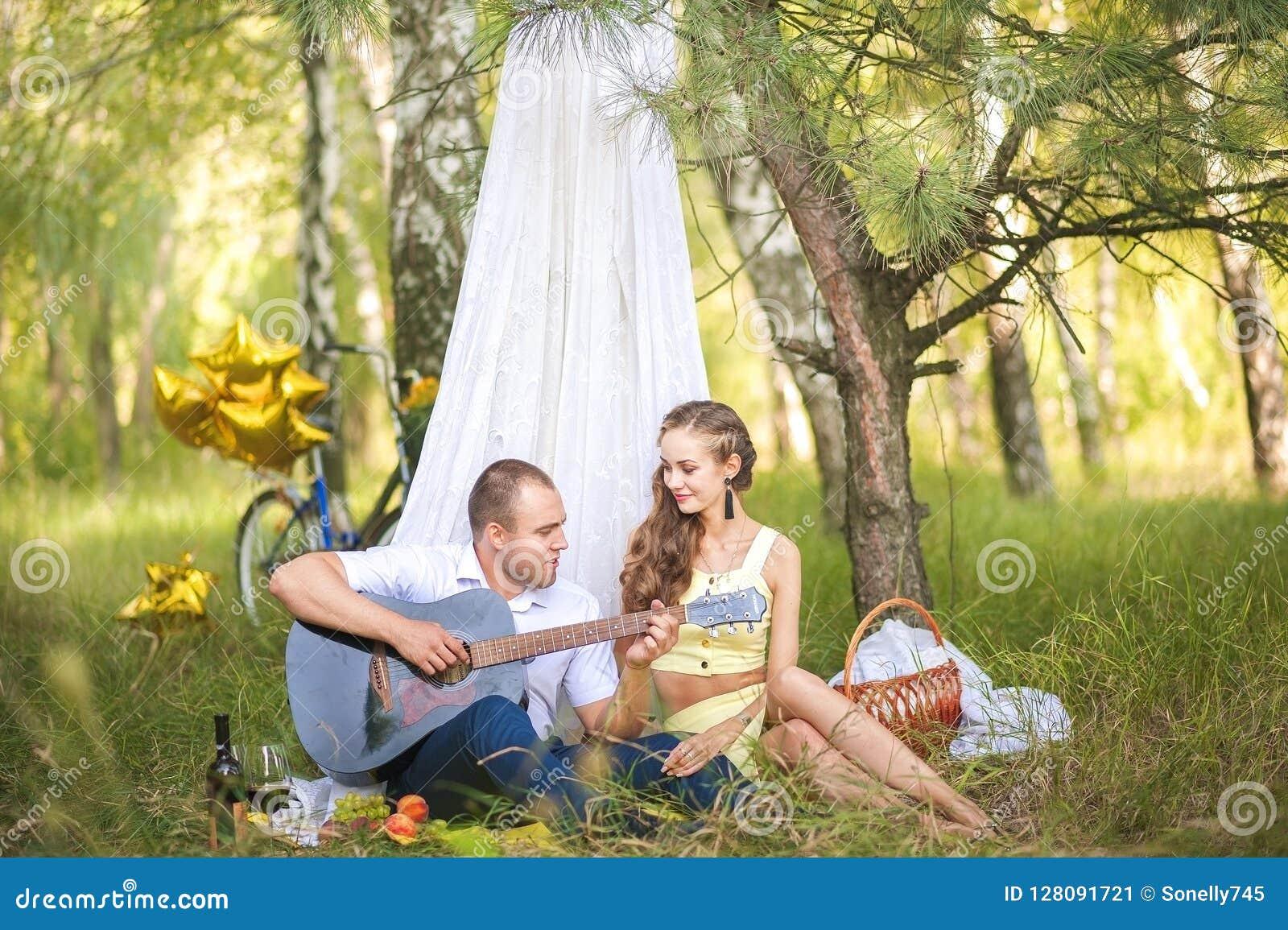 Um homem joga a guitarra amado Homem e mulher em uma cabana, o conceito do romance e idílio