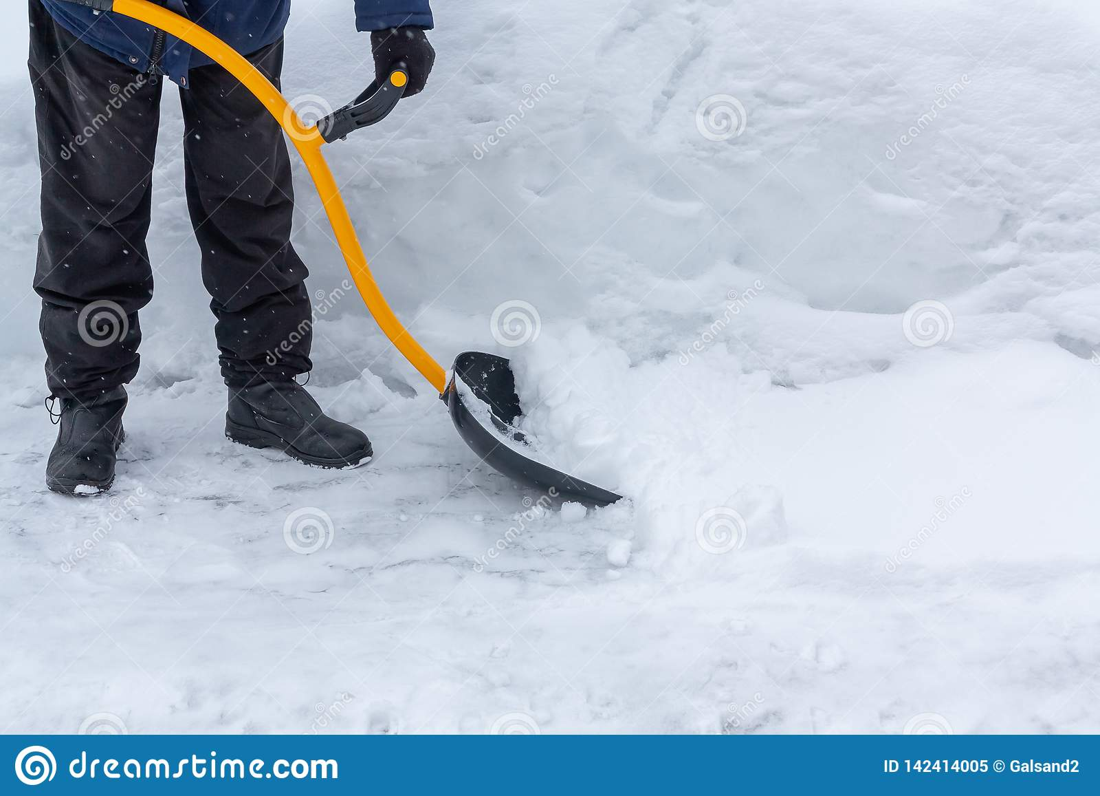 Um homem limpa a neve na jarda com uma pá após uma queda de neve pesada