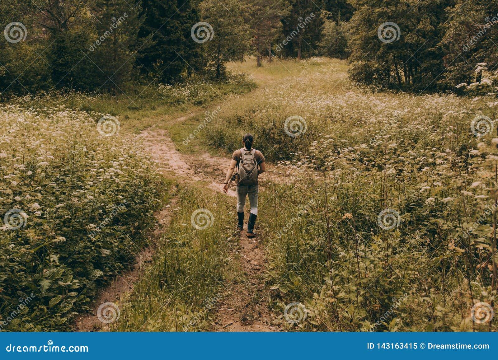 Um homem nas botas de borracha anda para trás através de um prado da flor