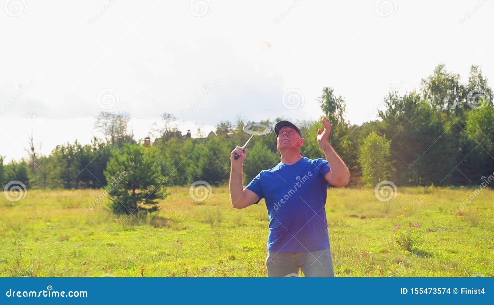 Um homem no campo dá a bola ao jogar badminton vídeos de arquivo