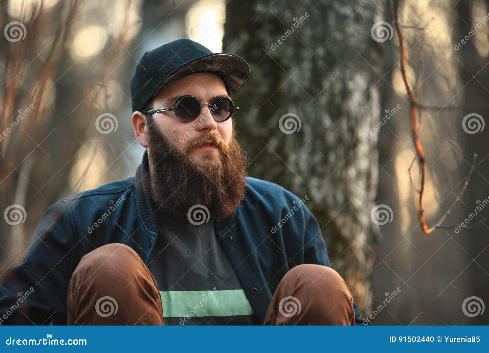 61dff683e7042 Um homem novo brutal com uma barba enorme nos óculos de sol e em um tampão  nas madeiras no por do sol lifestyle