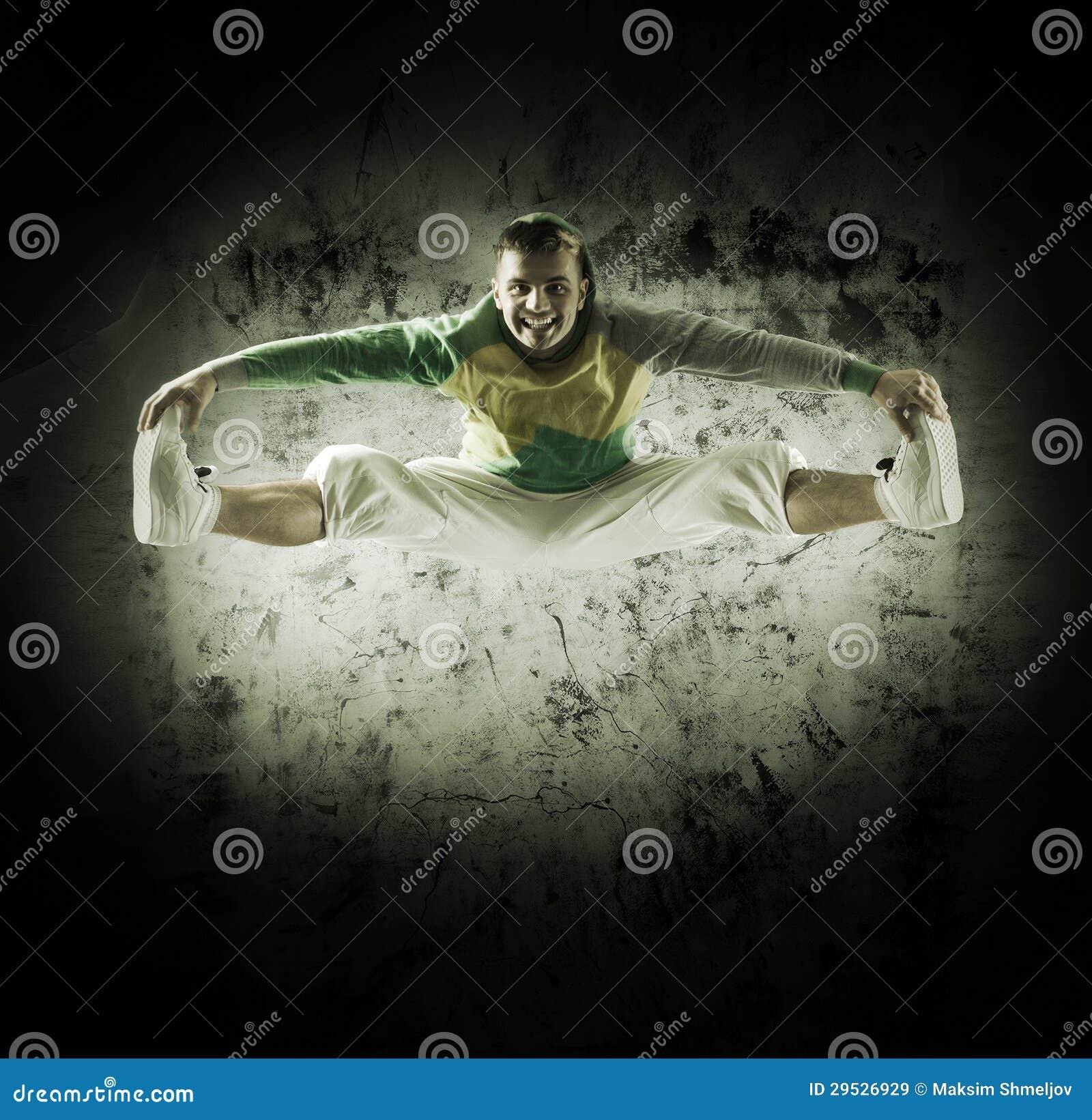 Um homem novo e desportivo que faz uma pose da dança moderna