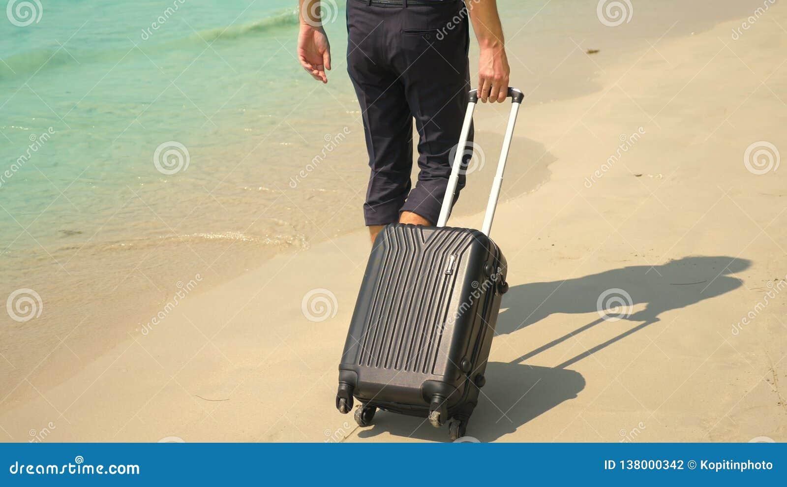 Um homem novo nas calças e em uma camisa clássica com uma mala de viagem anda ao longo da praia contra o contexto do mar de turqu