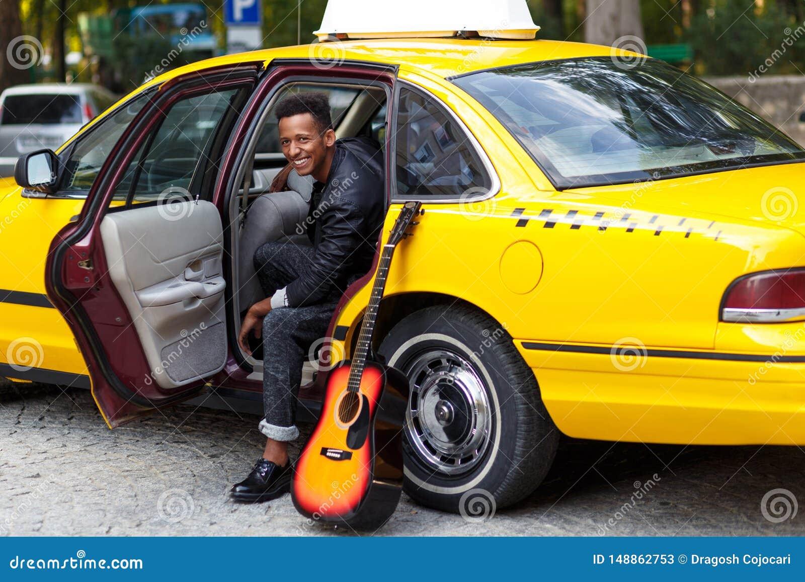 Um homem novo no carro com a porta aberta do carro amarelo, olhando e sorrindo, com pé esquerdo fora, perto da guitarra