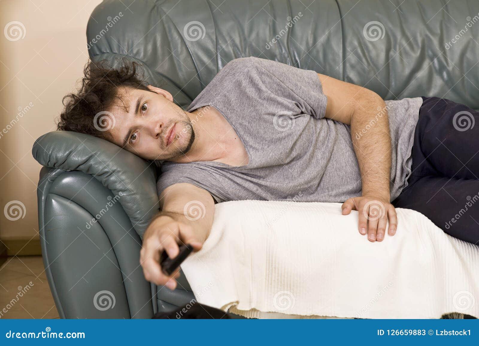 Um homem novo olha a televisão e muda os canais ao relaxar