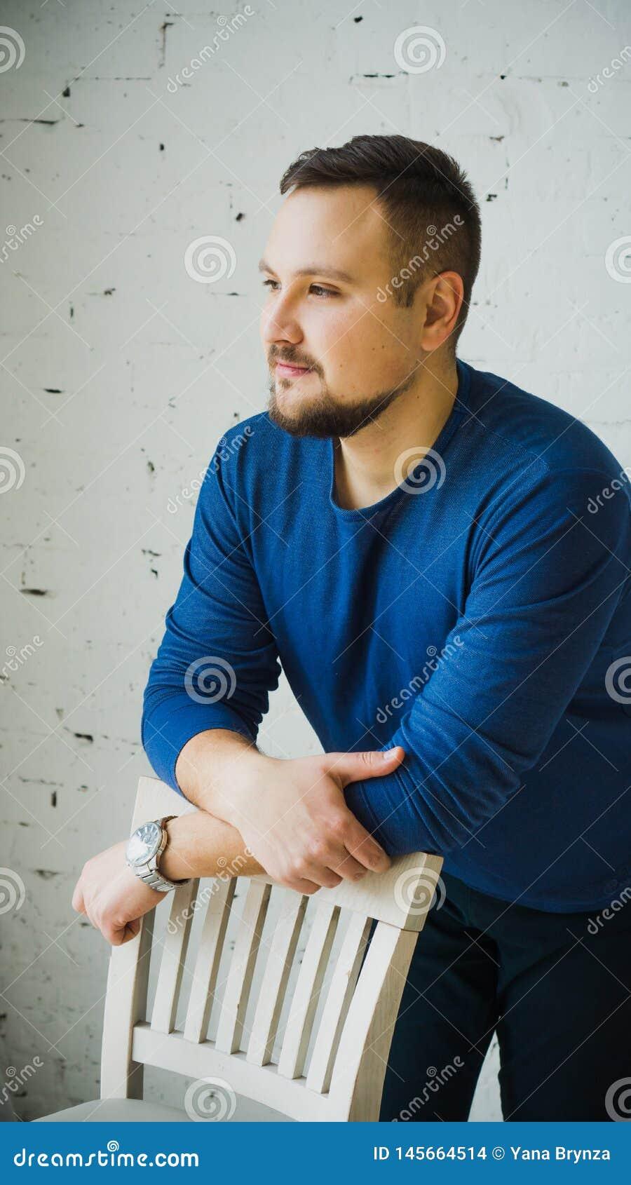 Um homem novo que inclina-se na parte de tr?s de uma cadeira olha ao lado contra uma parede de tijolo branca