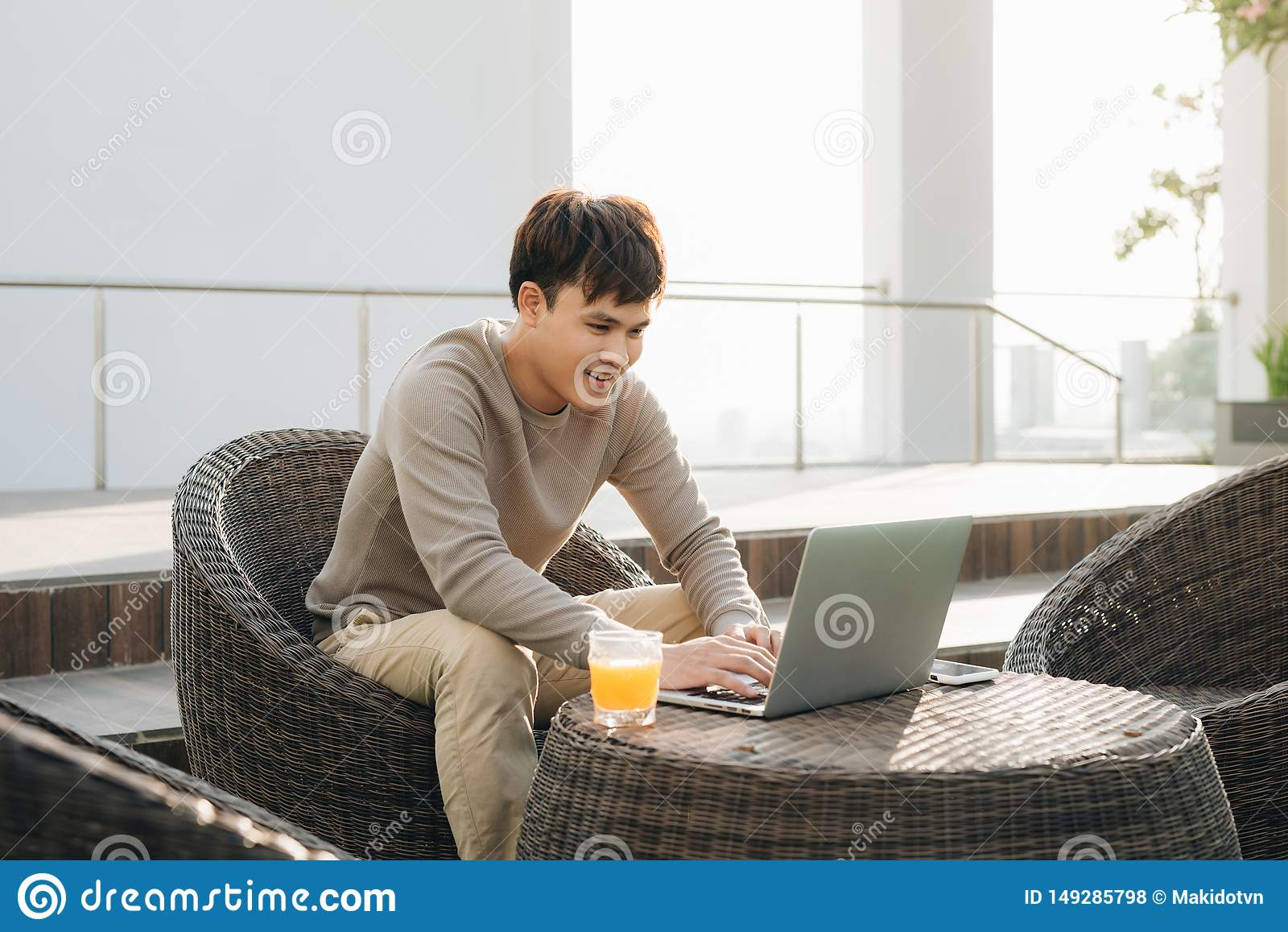 Um homem novo que usa o laptop ao sentar-se em um sof? fora