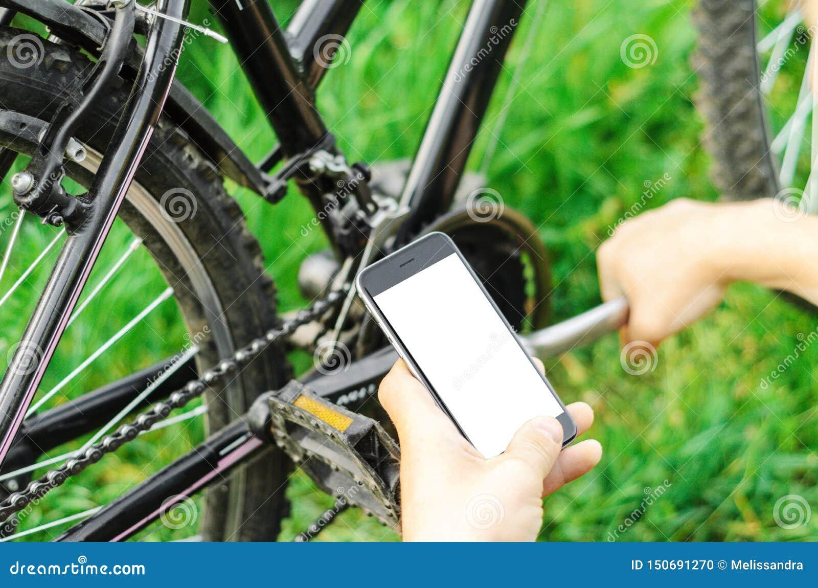 Um homem olha no telefone, reparando um Mountain bike em uma estrada de floresta Trabalho do reparo, mecânico