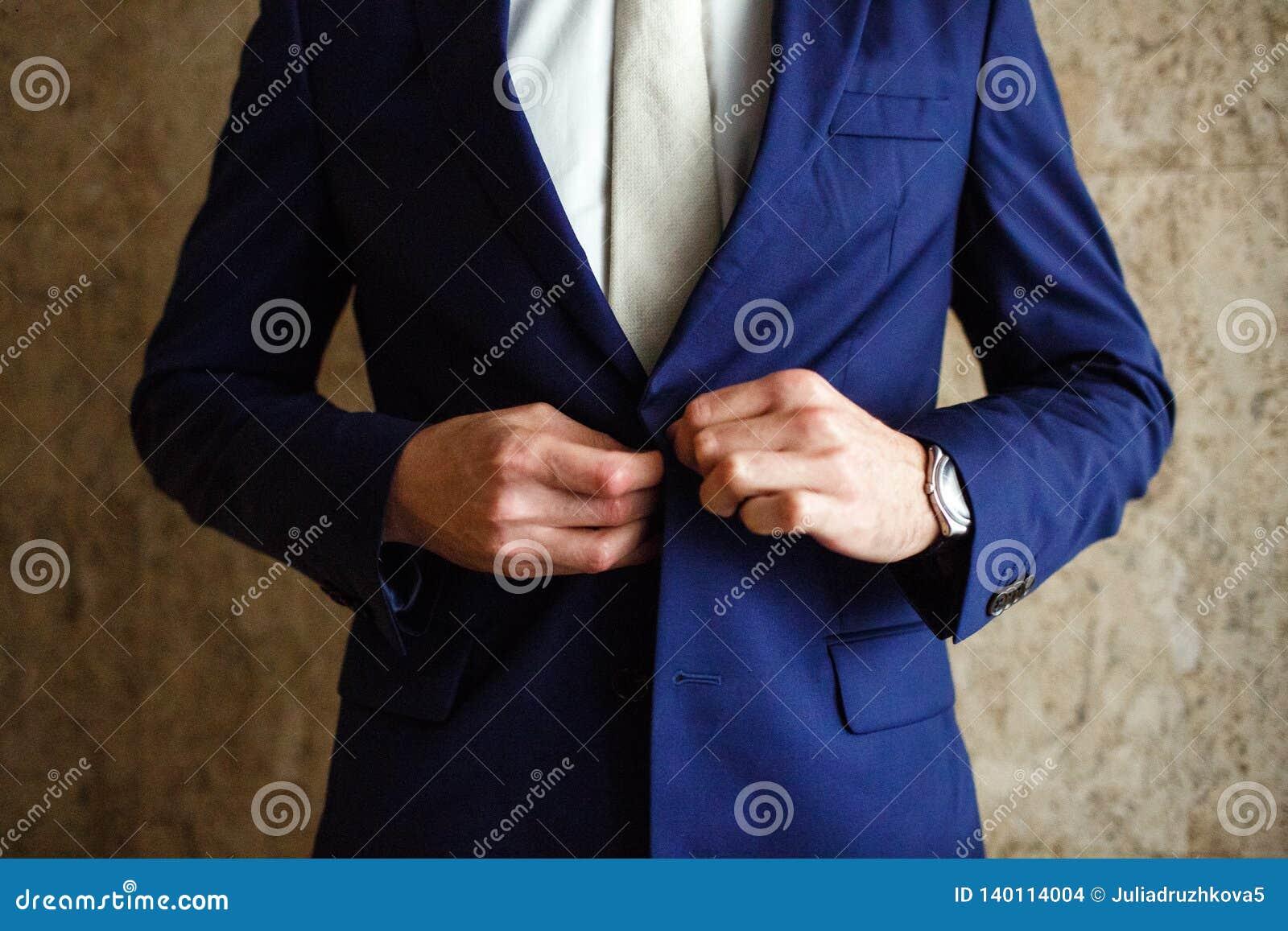 Um homem prende o casaco azul dos botões em sua mão seu relógio