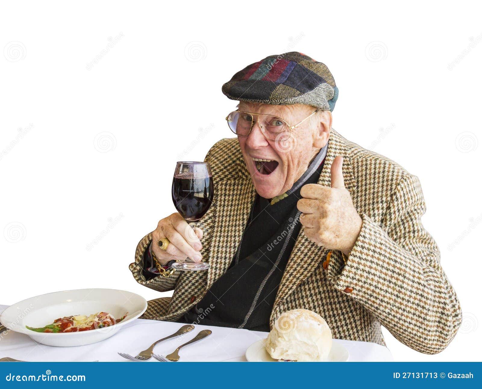 Um homem que dá os polegares acima da aprovaçã0 para o vinho e o alimento