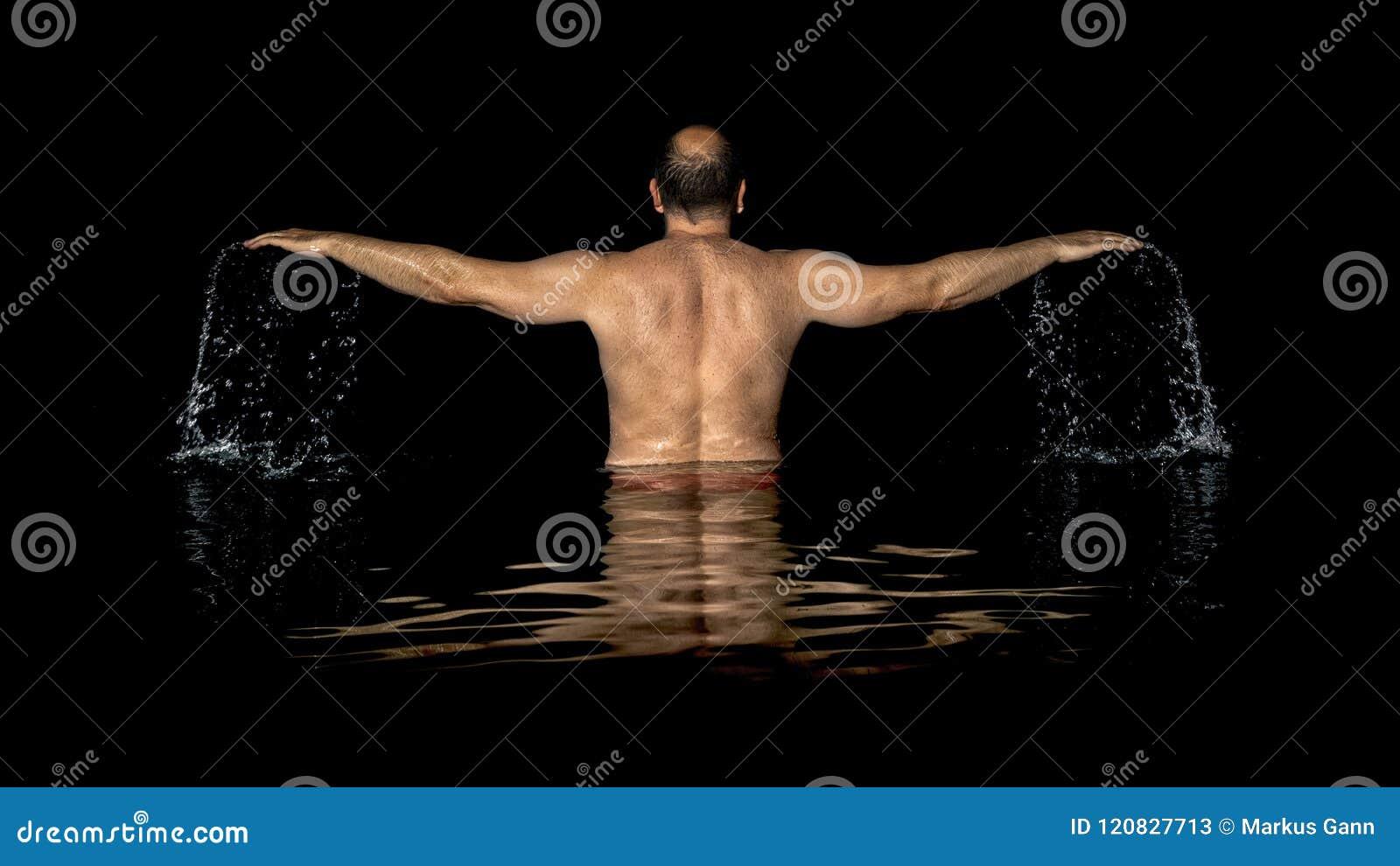 Um homem que está dentro da água e das propagações seus braços