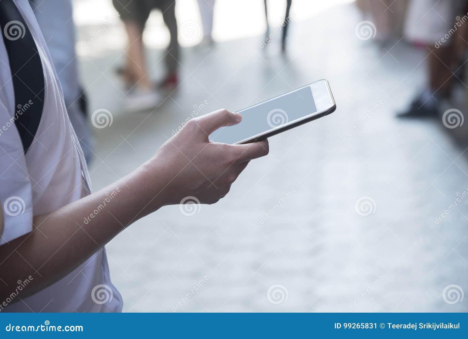 Um homem que guarda um telefone celular