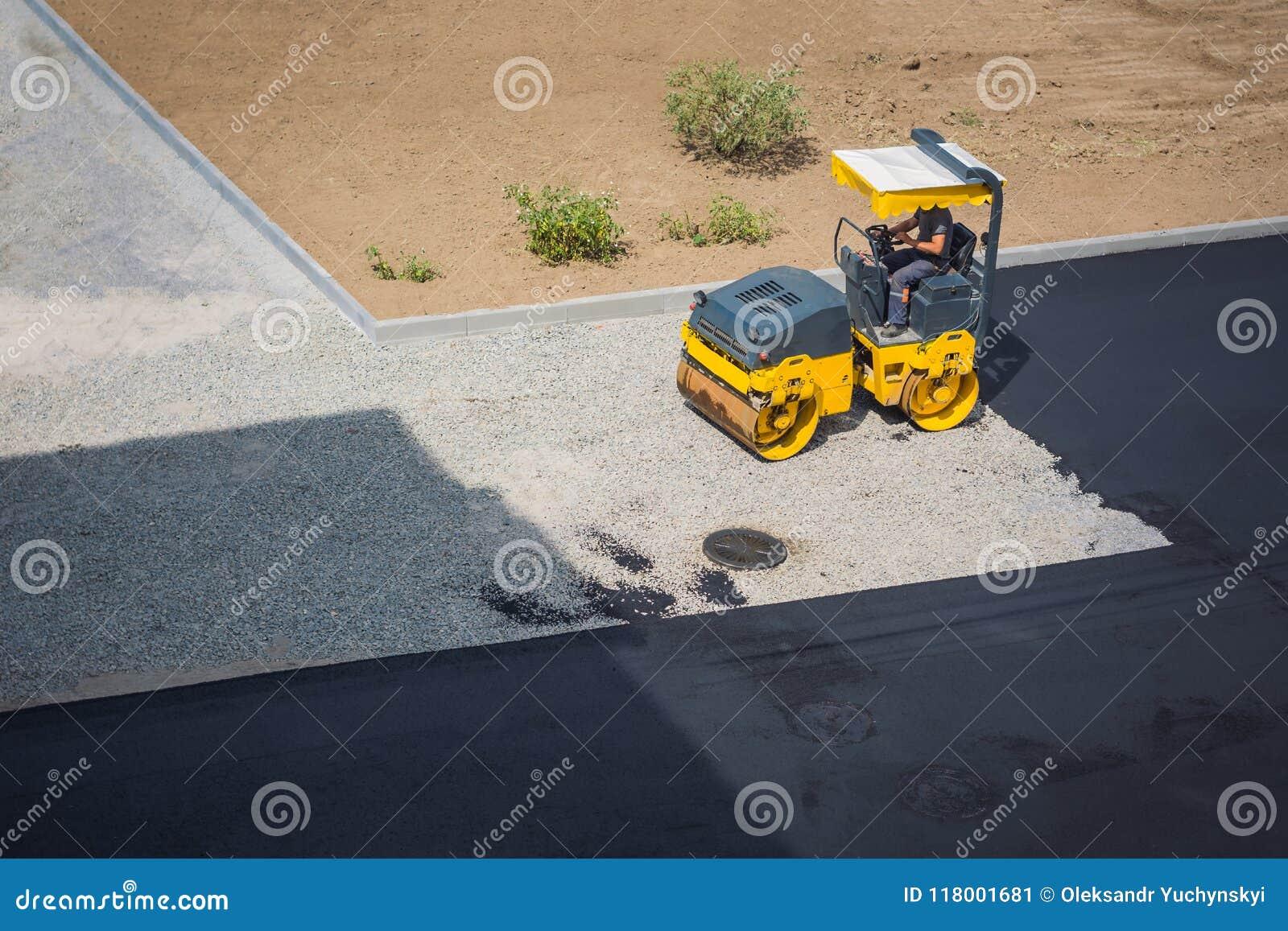 Um homem que senta-se em um minitruck está forçando a entulho para a instalação mais adicional do asfalto em uma estrada quebrada