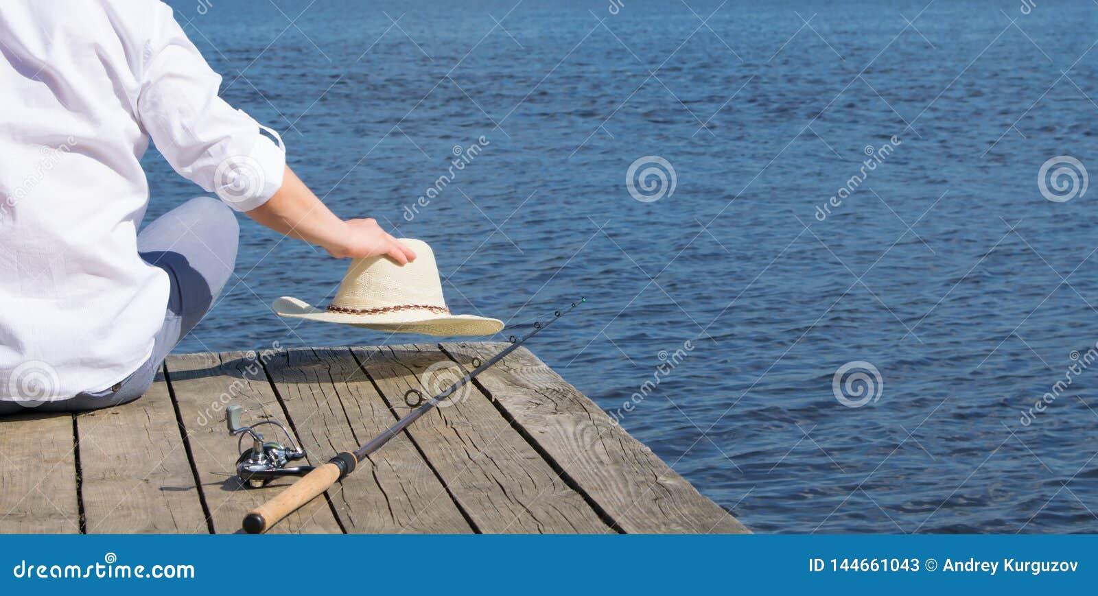 Um homem que senta-se no cais e que guarda um chapéu, encontrando-se ao lado de uma vara de pesca, no fundo do lago
