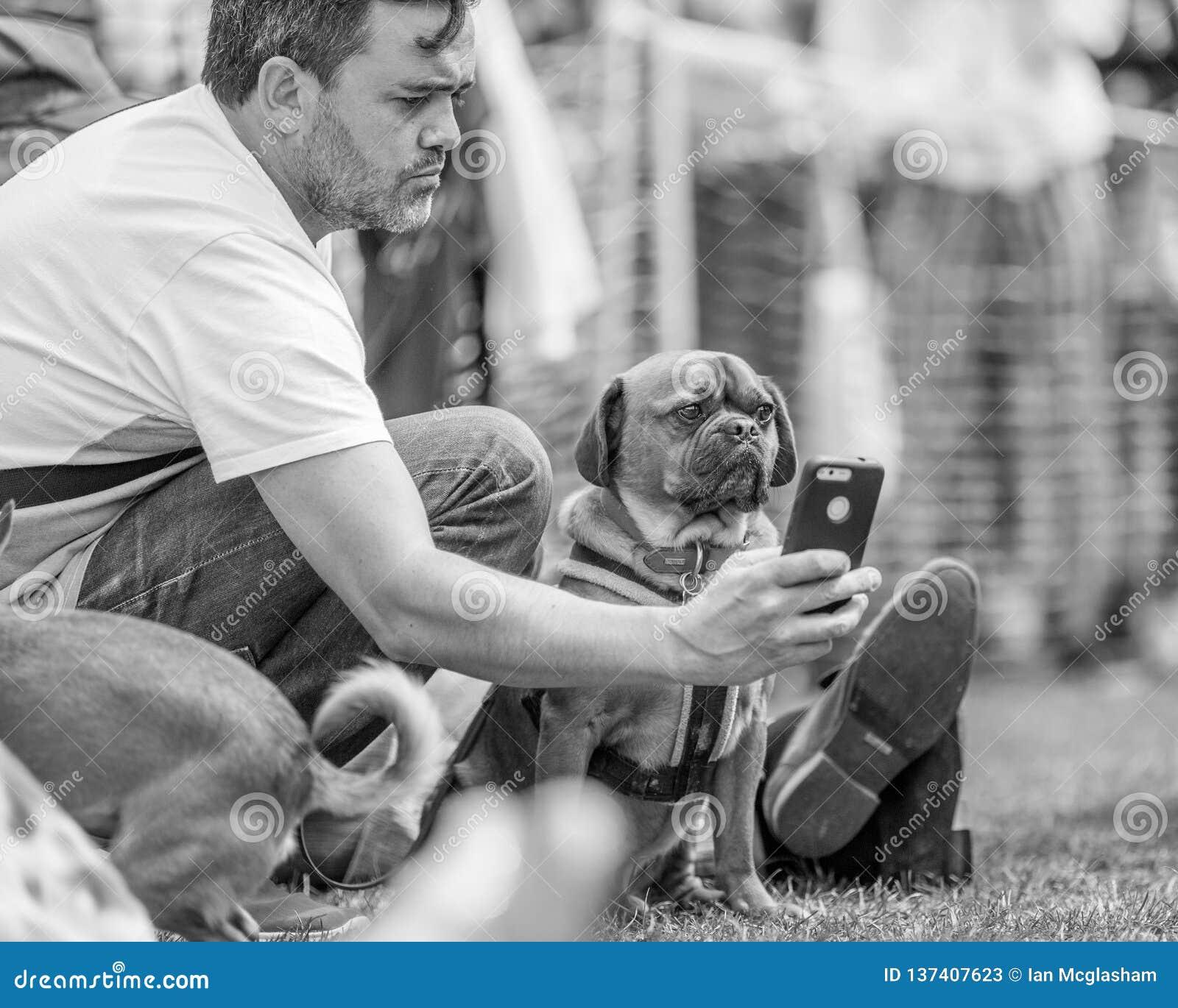 Um homem que toma um selfie com um cão no parque em uma exposição de cães