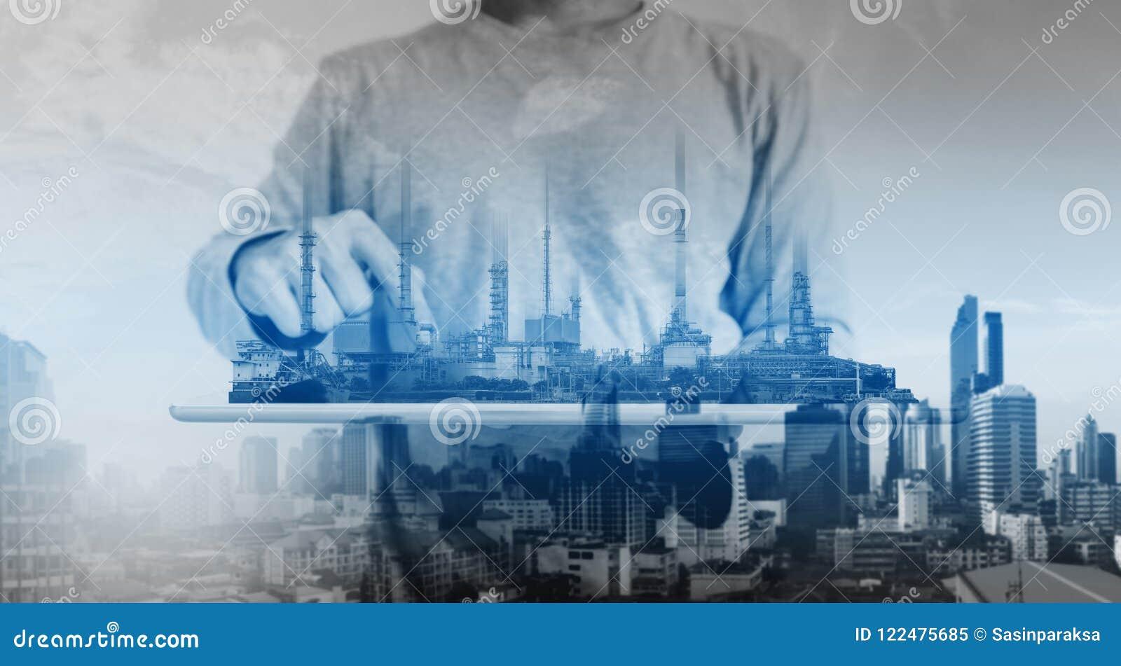 Um homem que trabalha na tabuleta digital, com central elétrica, holograma das construções da fábrica da indústria da refinaria d