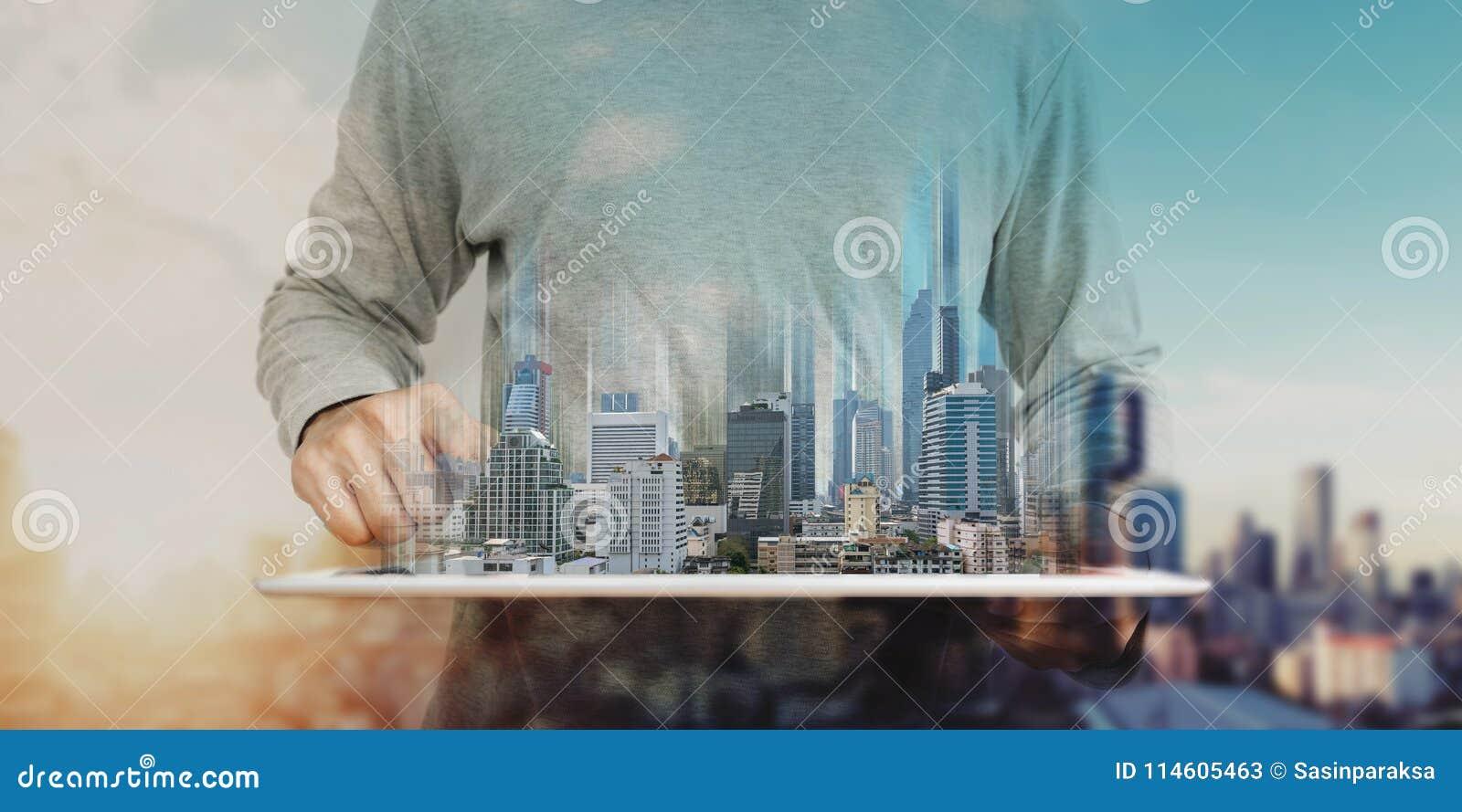 Um homem que usam a tabuleta digital, e holograma moderno das construções Negócio dos bens imobiliários e conceito da tecnologia
