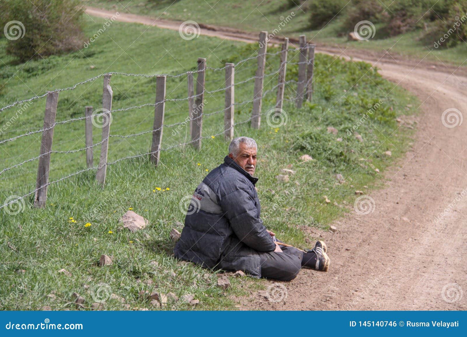 Um homem rural cansado que senta-se ao lado da estrada no assoalho, uma exploração agrícola é encerrado com uma cerca, Irã,