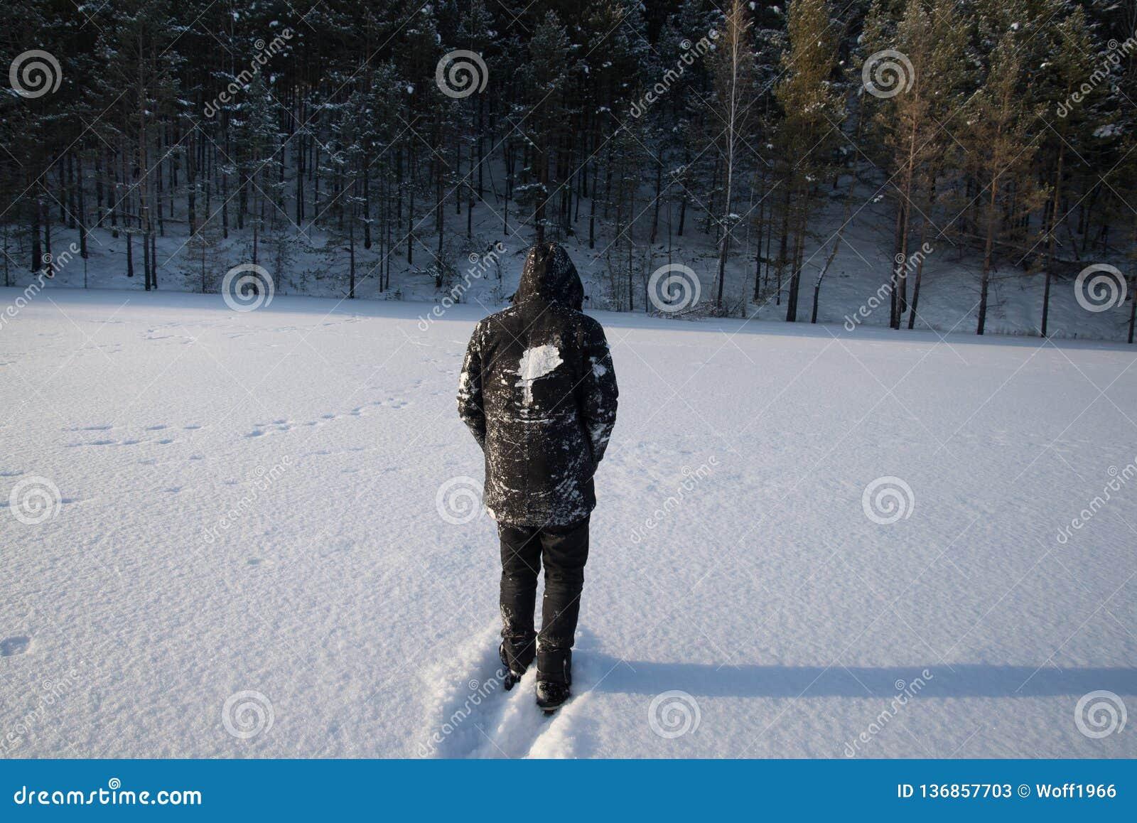 Um homem só anda na neve Silhueta dramática de um homem que anda em um esclarecimento nevado na floresta friamente