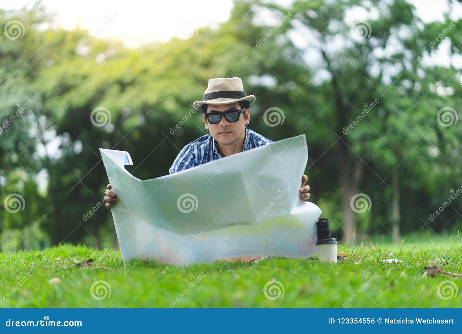 Um homem superior do viajante feliz senta-se em Forrest, abrindo um mapa