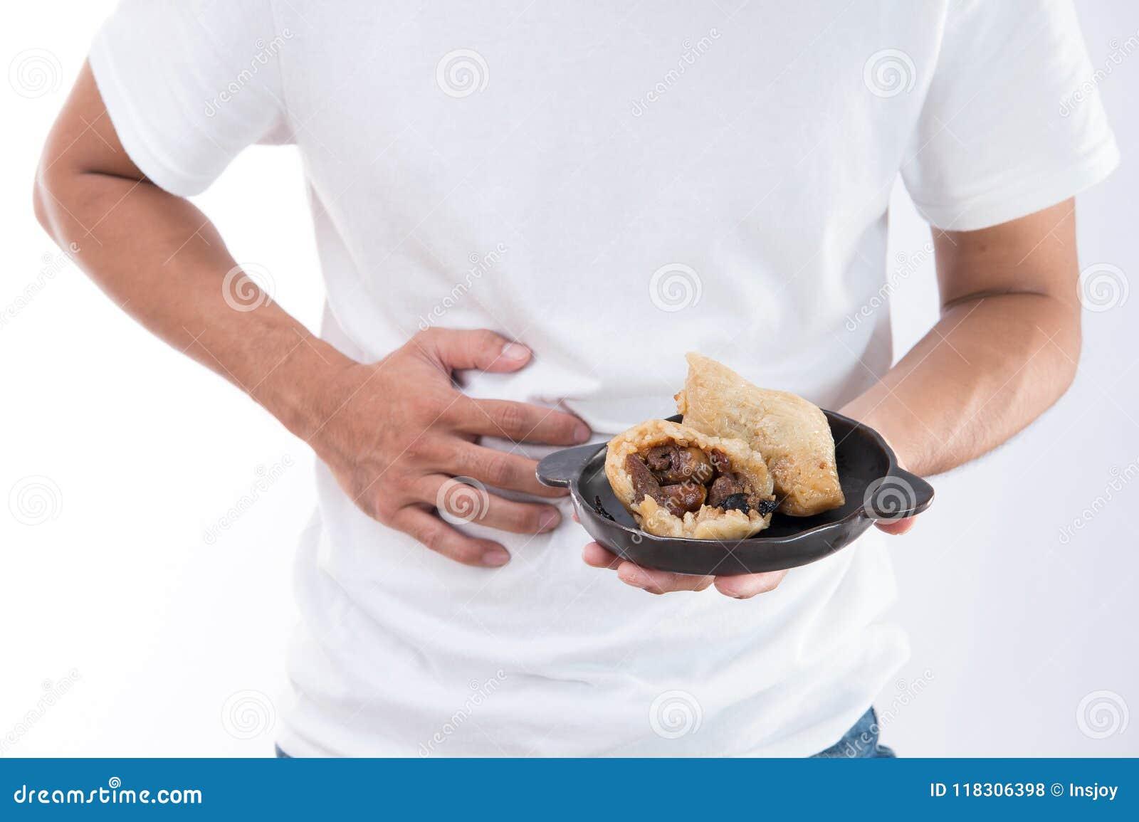 Um homem tem uma dor de estômago após ter comido a bolinha de massa deliciosa do zongzirice em Dragon Boat Festival, alimento tra
