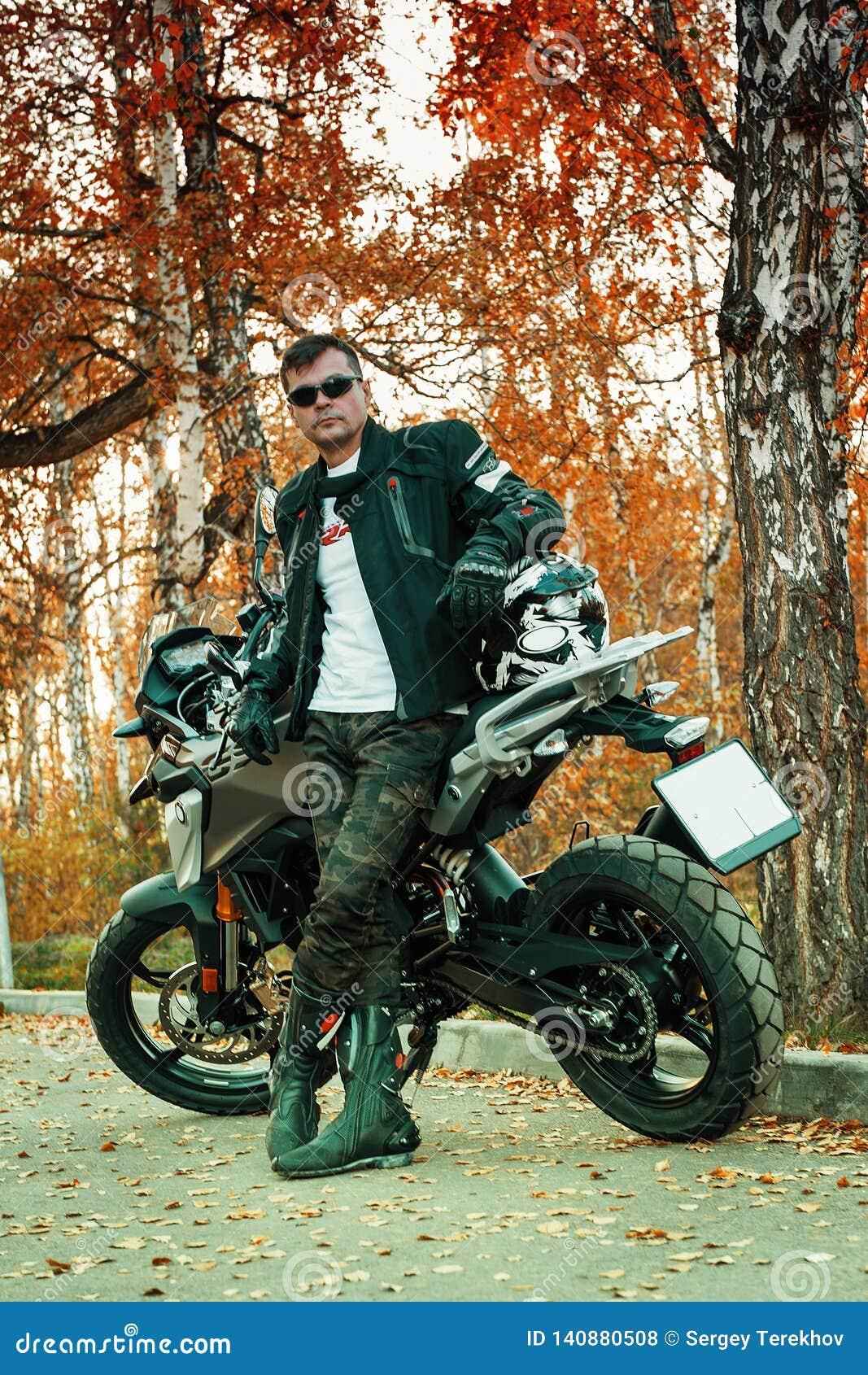 Um indivíduo atrativo e uma jovem mulher em um equipamento de couro preto com uma motocicleta