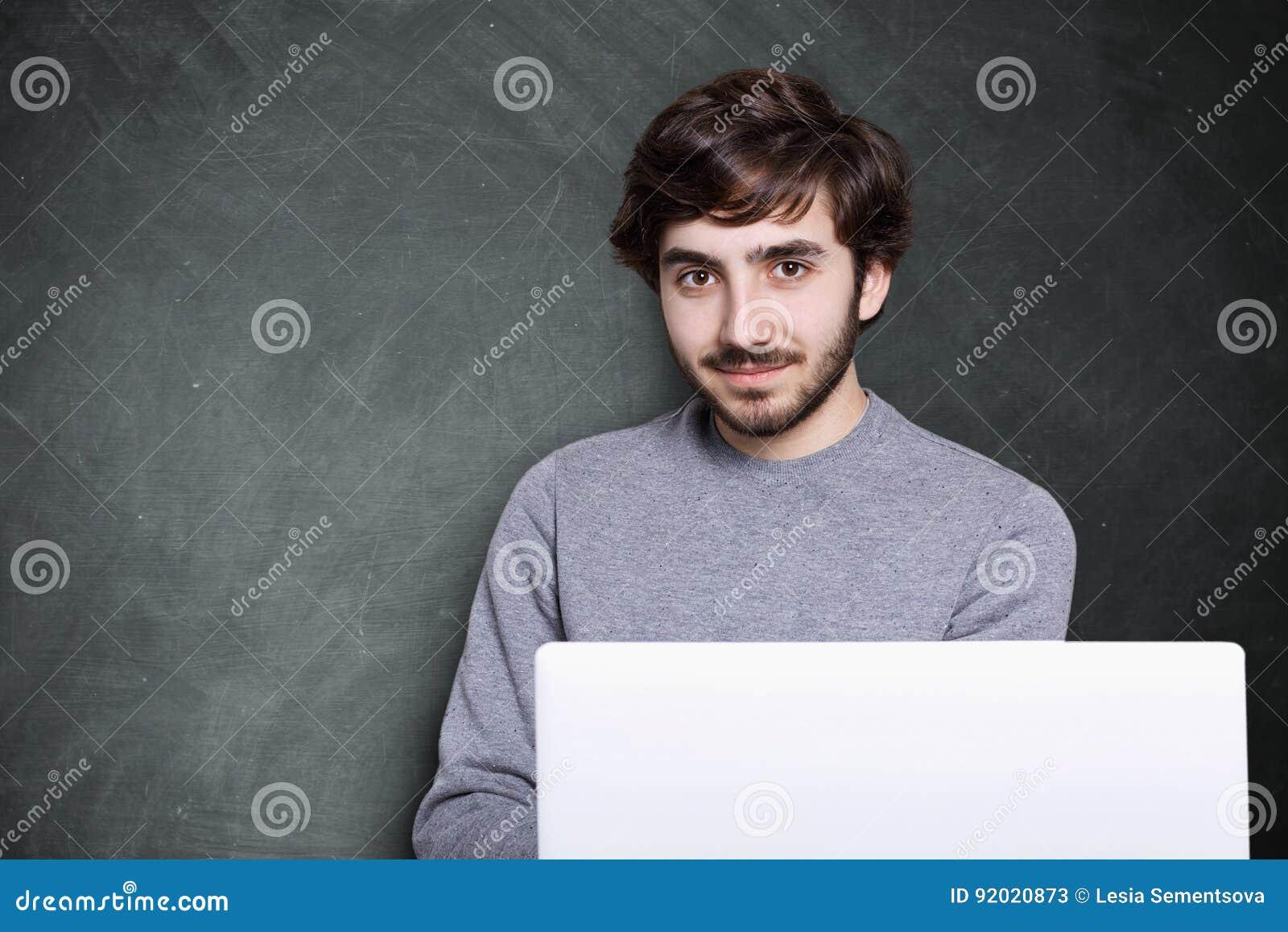 Um indivíduo atrativo seguro com barba escura e penteado à moda