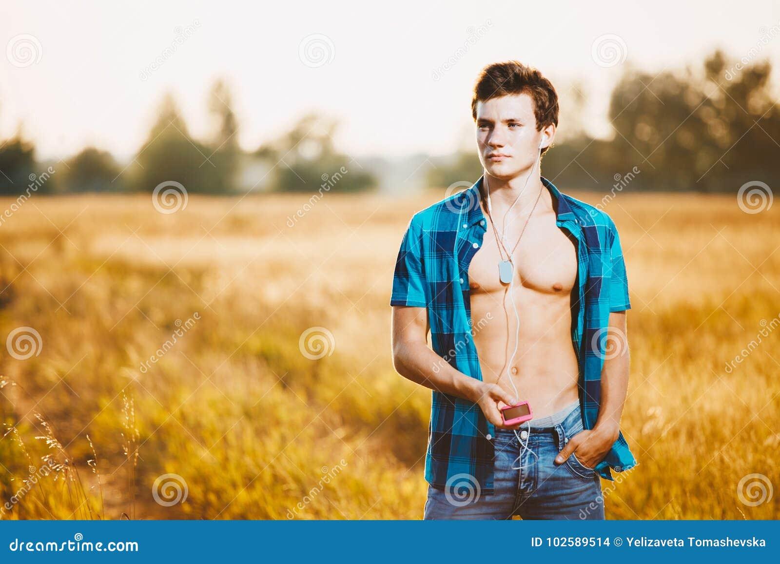 Um indivíduo caucasiano novo considerável com um corpo muscular vestiu-se no short de uma camisa desabotoada azul e da sarja de N