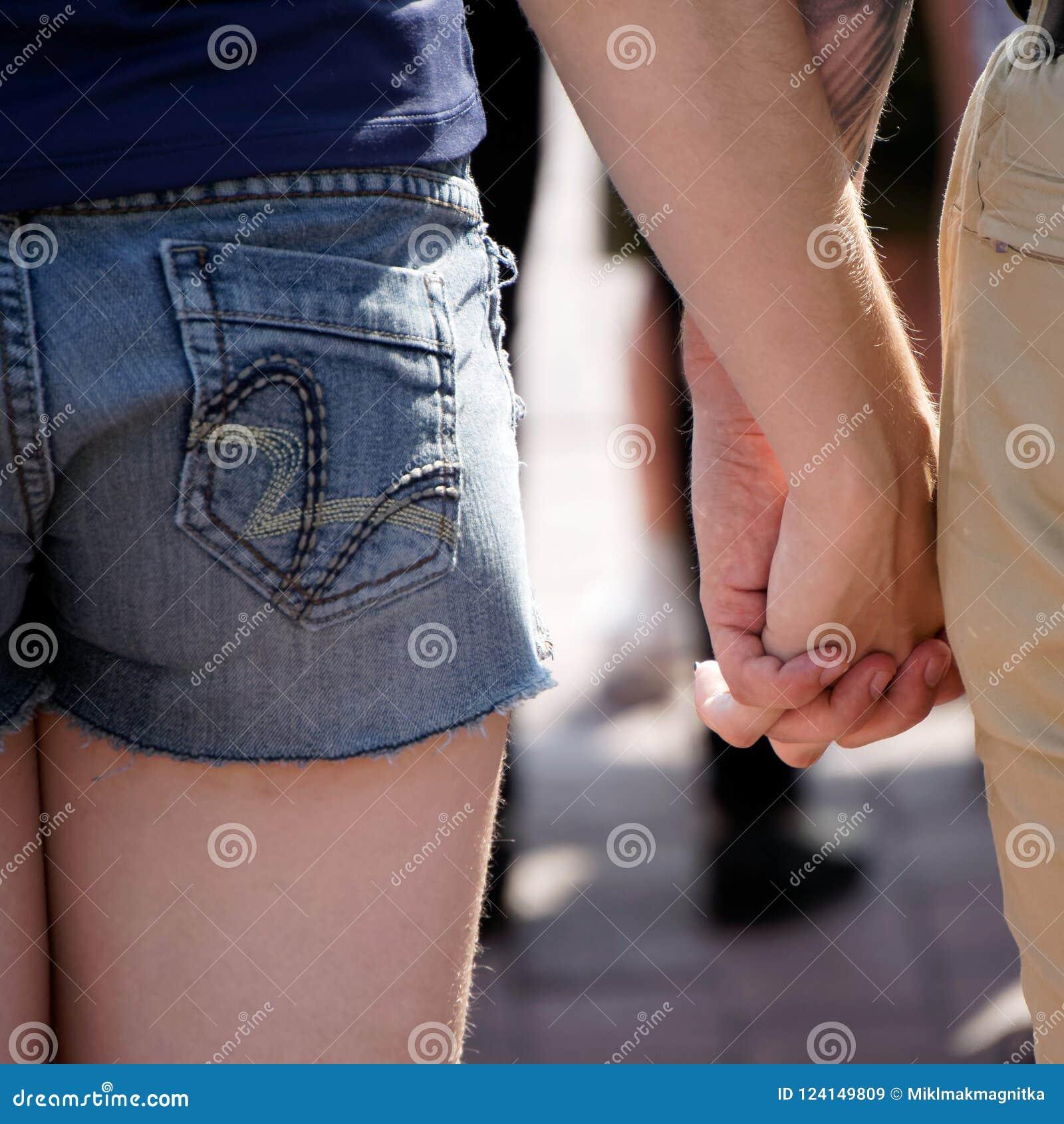 Um indivíduo e uma menina estão guardando as mãos em uma multidão