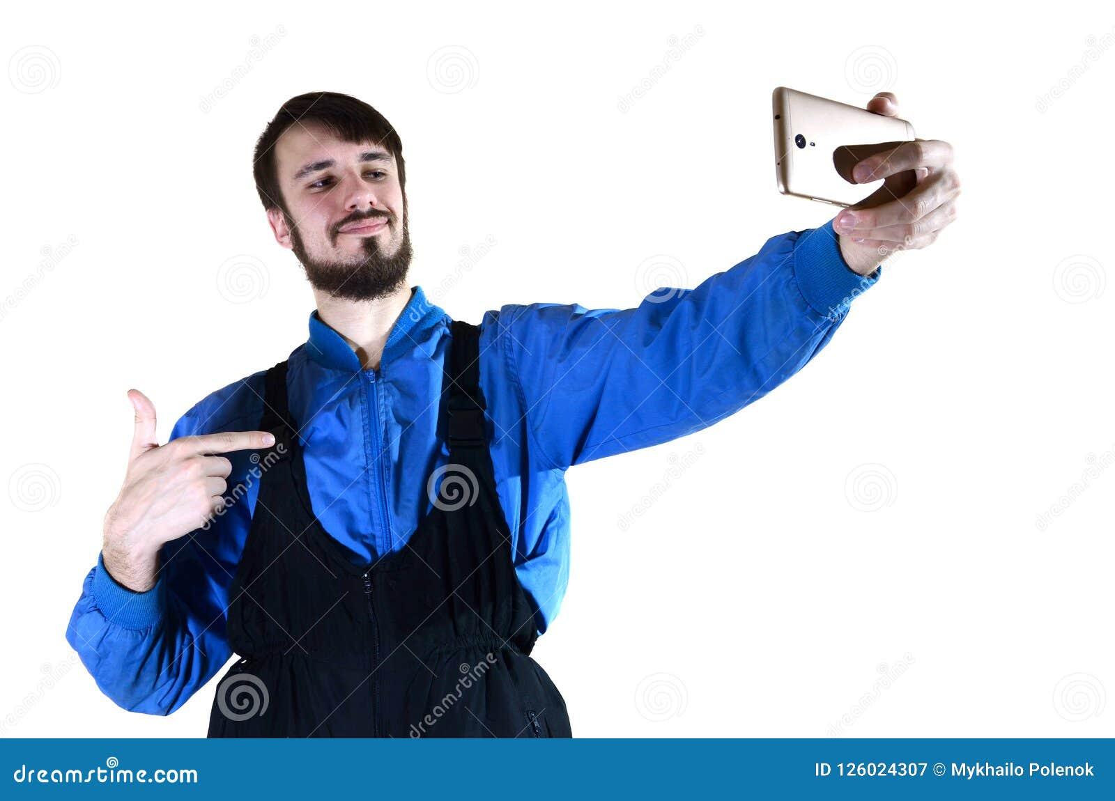 Um indivíduo farpado novo em um uniforme do trabalho faz um selfie em um smartphone moderno, apontando a si mesmo com seu dedo