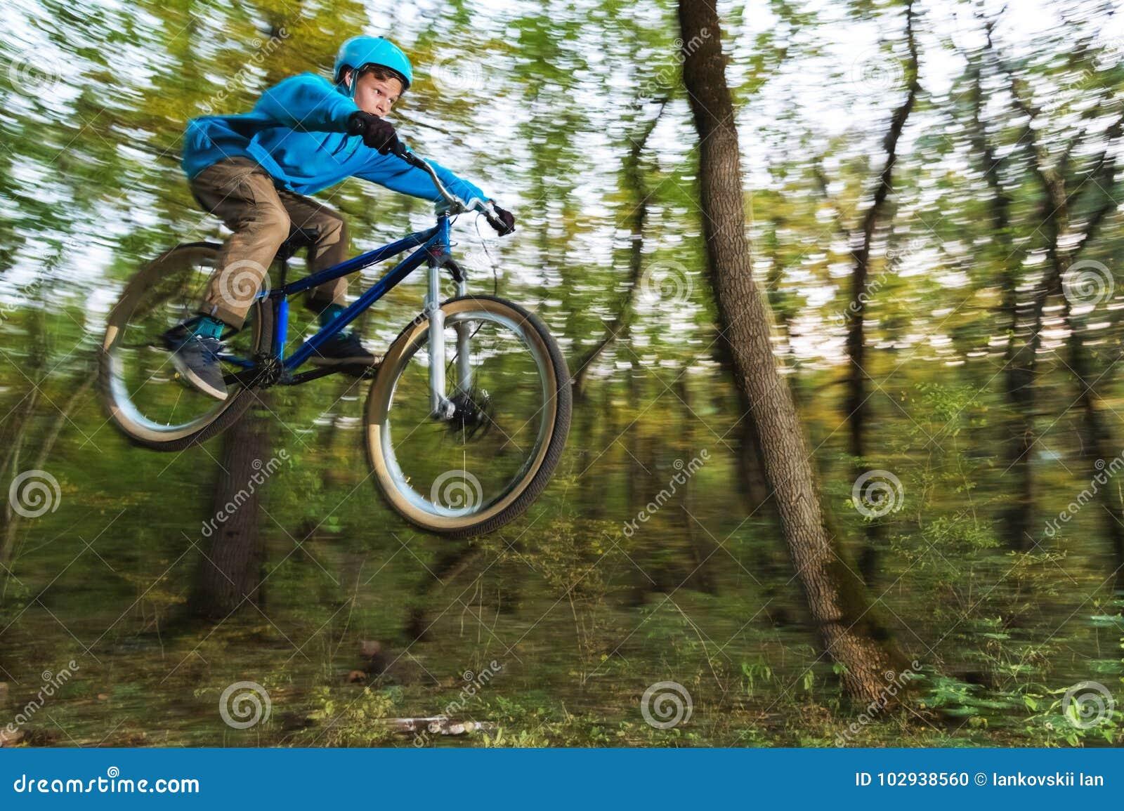 Um indivíduo novo em um capacete voa aterrado em uma bicicleta após o salto de um retrocesso