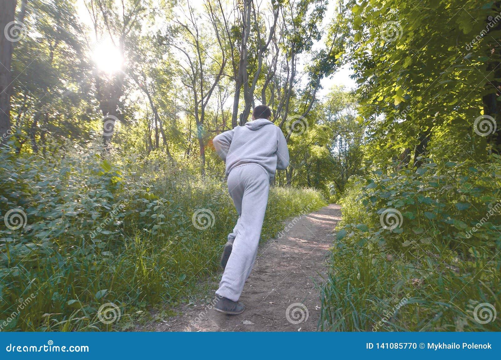 Um indivíduo novo em um terno cinzento dos esportes corre ao longo do trajeto entre
