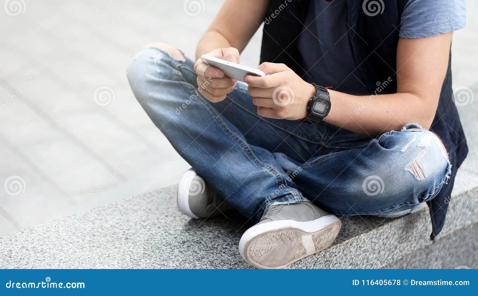 Um indivíduo novo usa seu smartphone ao sentar-se no asfalto