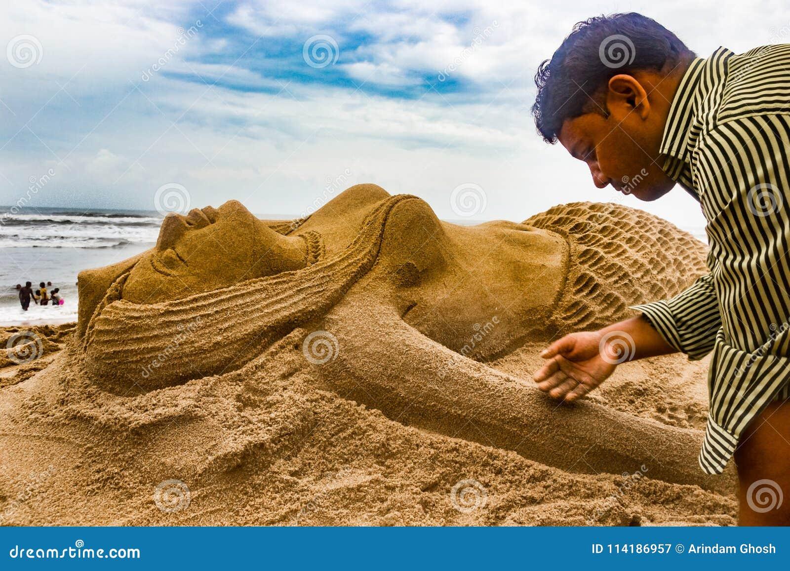 Um indivíduo que faz uma estátua da areia da sereia na arte arenosa do seabeach