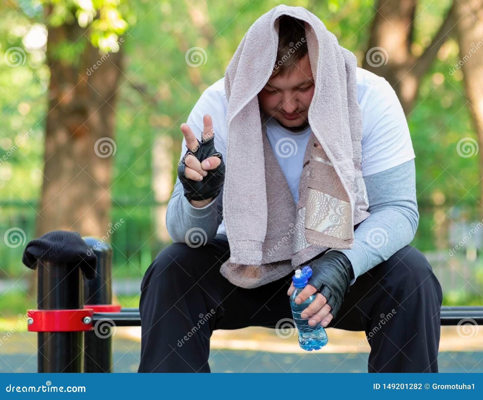 Um indiv?duo novo na roupa brilhante dos esportes com uma toalha em sua cabe?a e uma garrafa da ?gua em suas m?os est? sentando-s